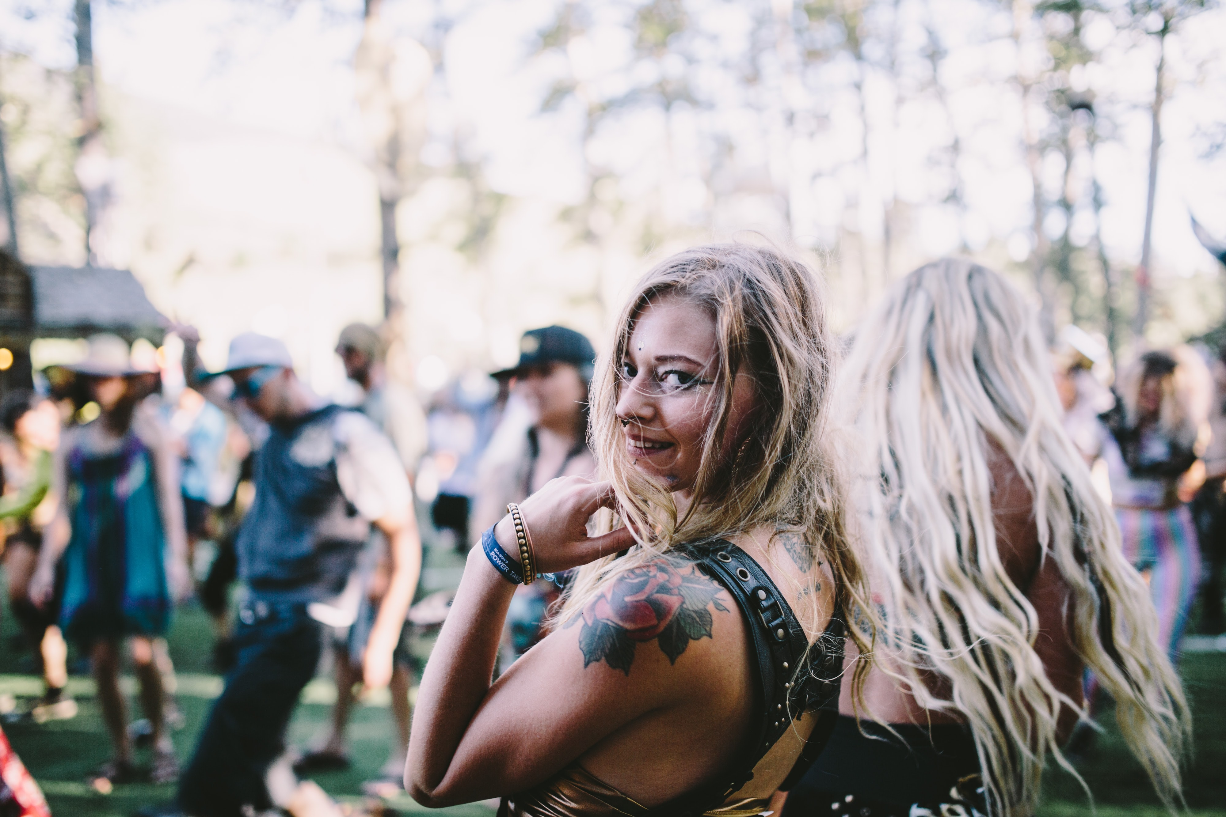 A blond woman with a rose tattoo on her arm looking back at the camera at an outdoor party