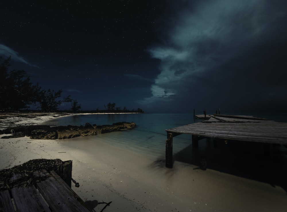 brown wooden dock and body of water under black sky during nighttime