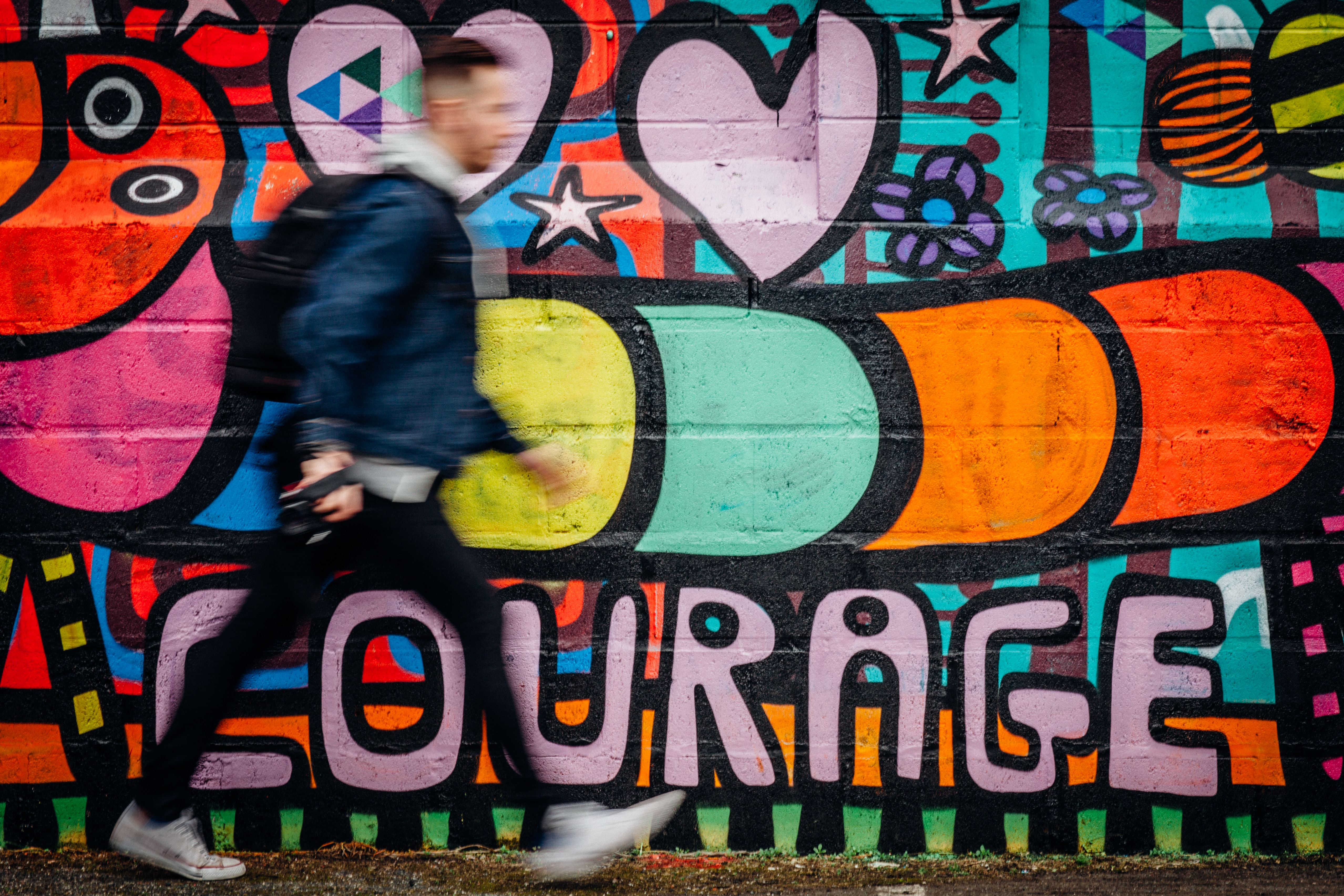 man walking beside graffiti wall