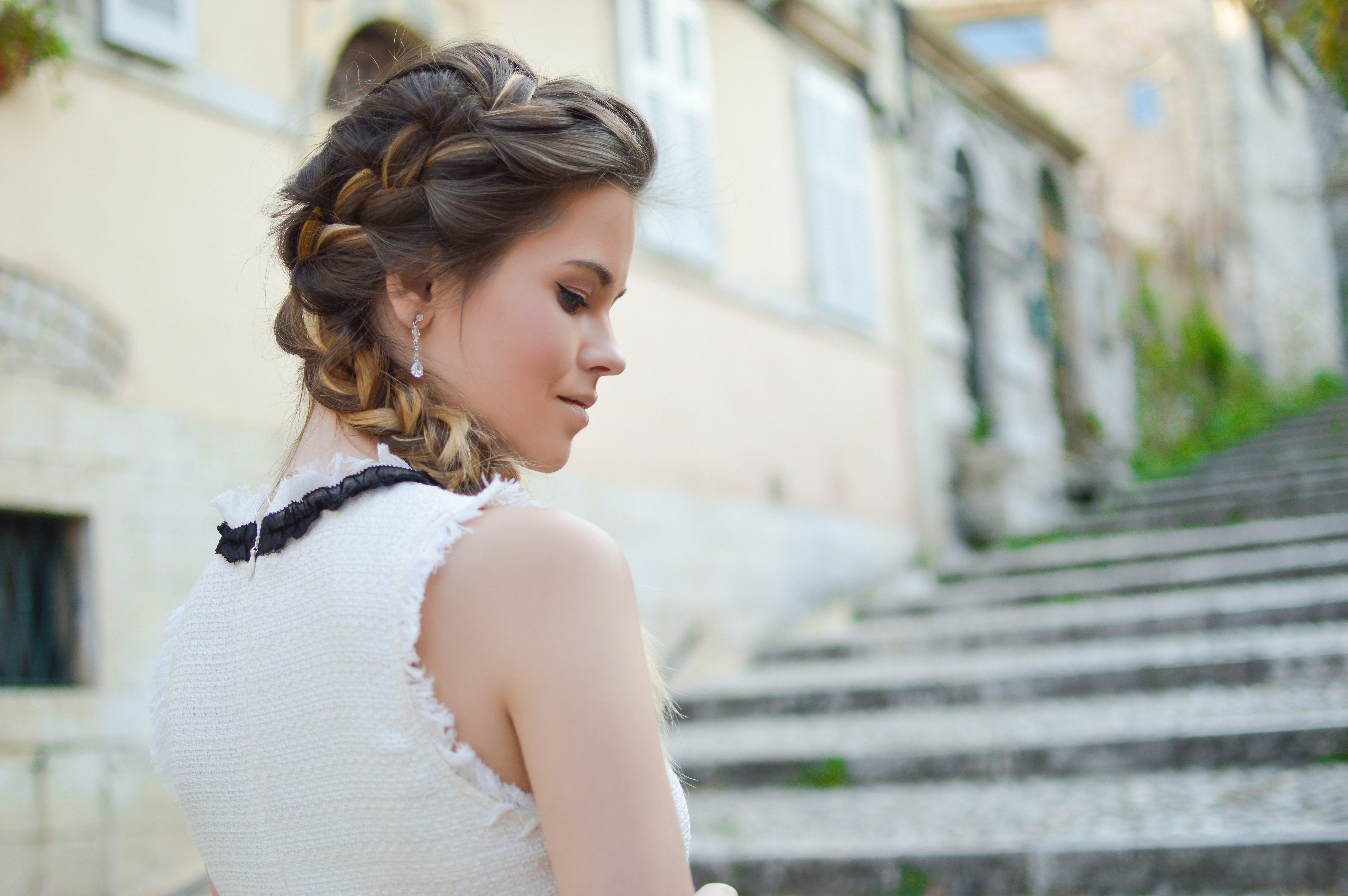 Woman with a french braid hairstyle smiling on a staircase