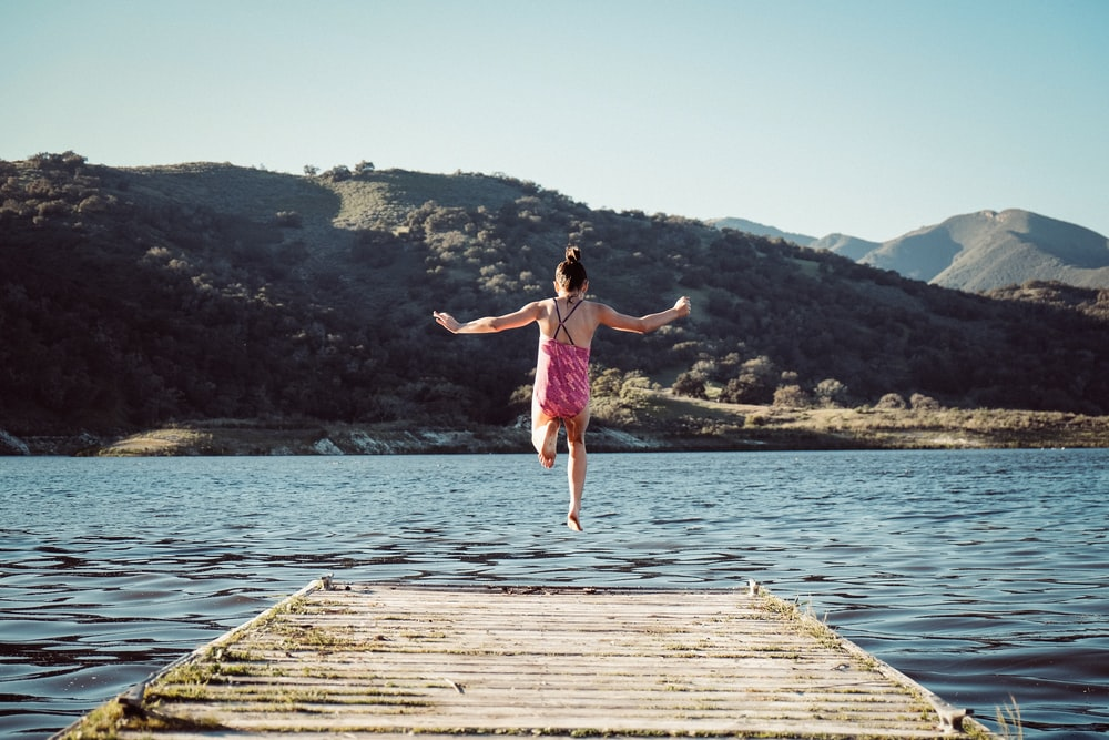 woman wearing pink top jumping towards water during daytime