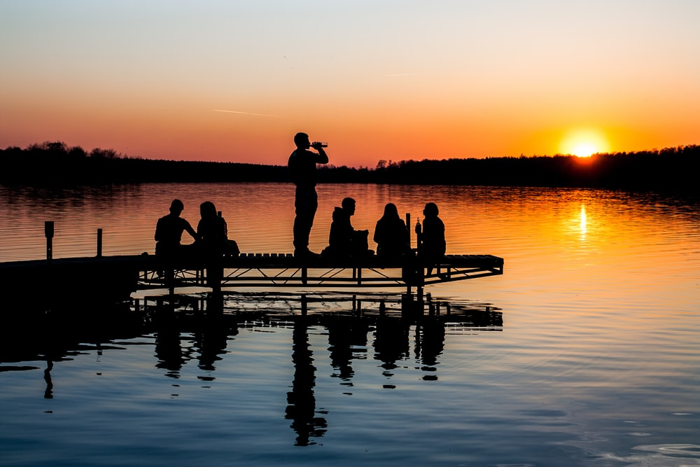 group of people on wooden dock during sunset in silhouette photography