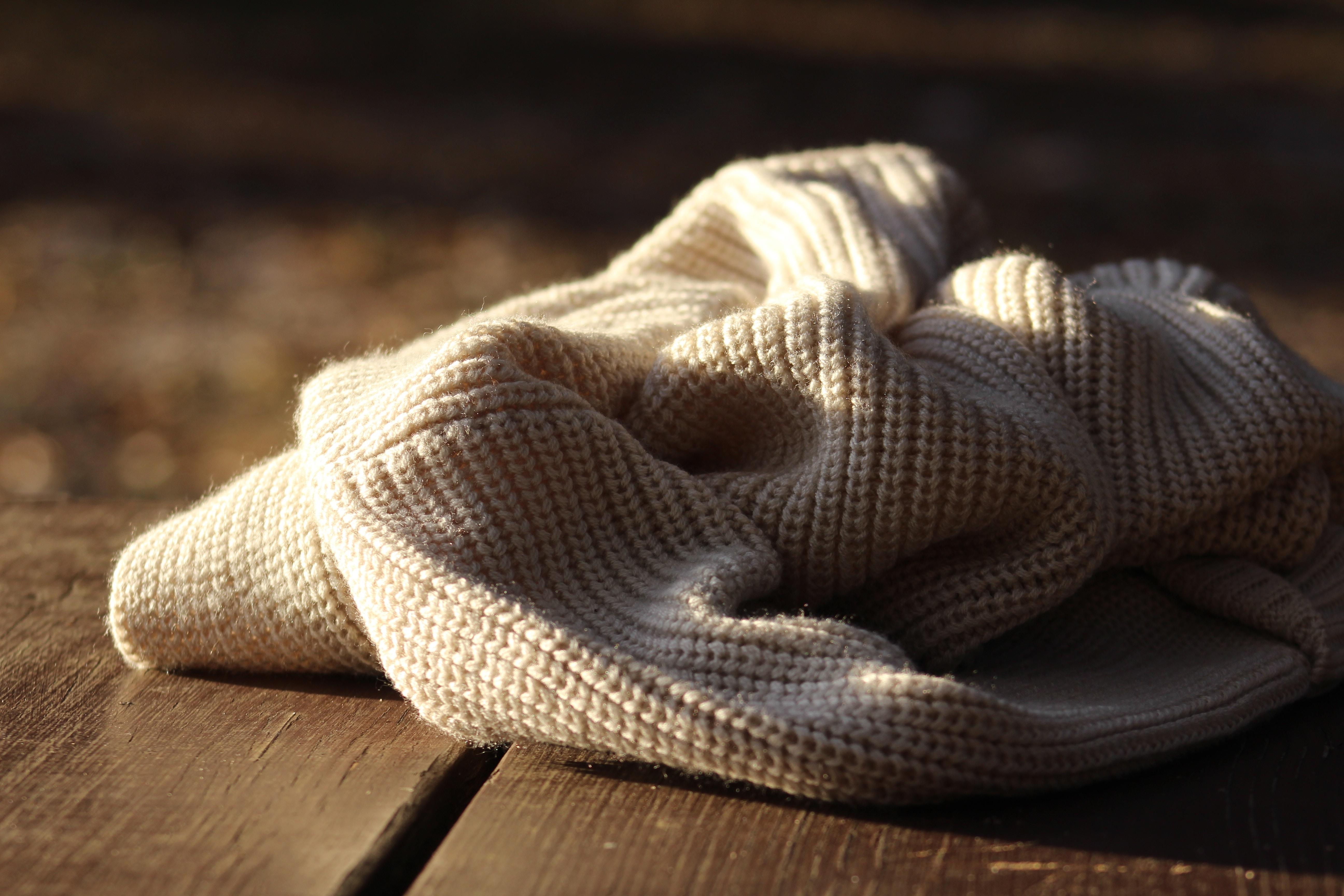 white textile on wooden plank