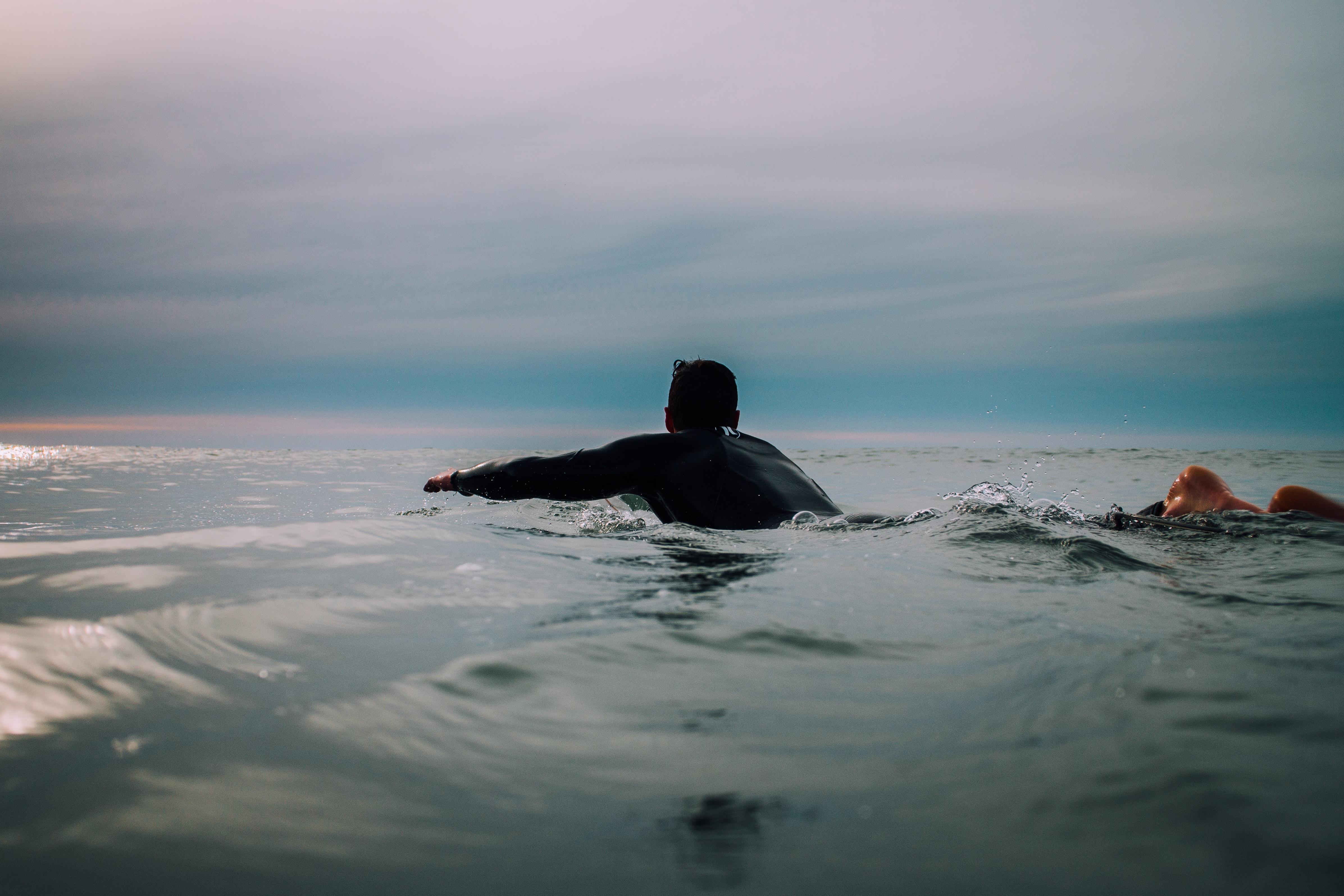 A male surfer swimming in a calm sea under a cloudy sky in Raglan