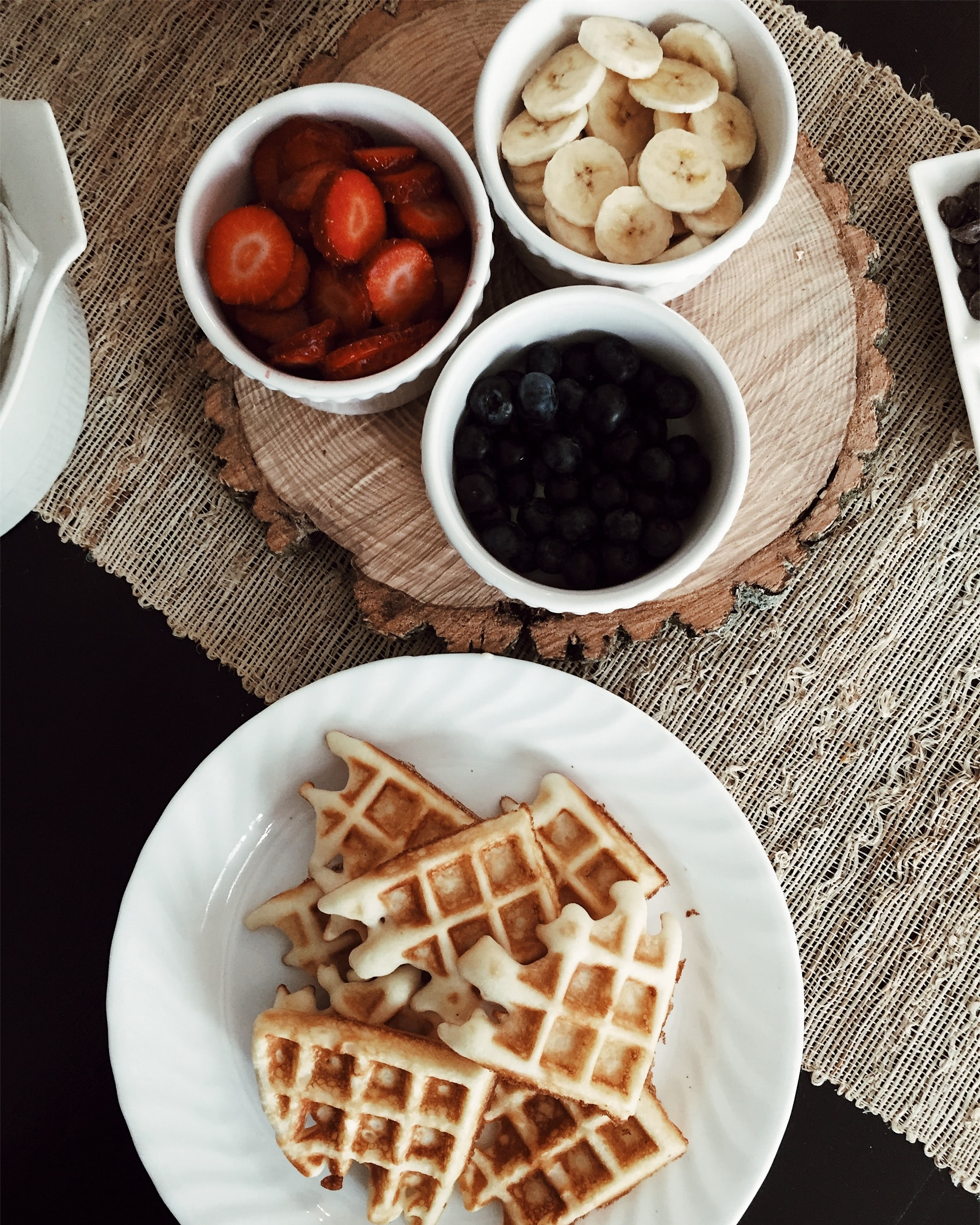 photo of waffles beside bowls of strawberries, banana, and black berries