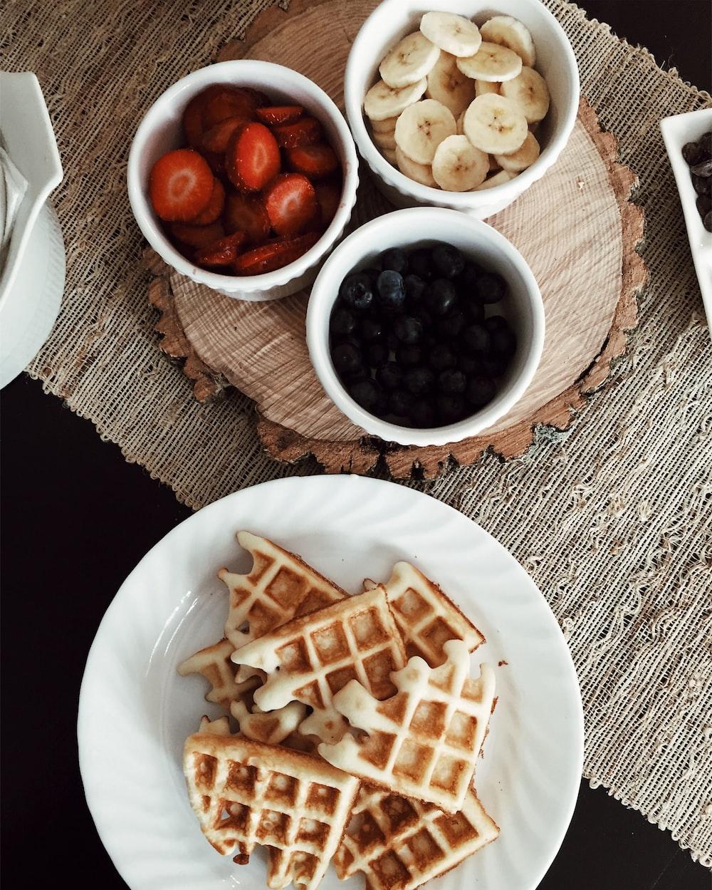 photo of waffles beside bowls of strawberries, banana, and black berries
