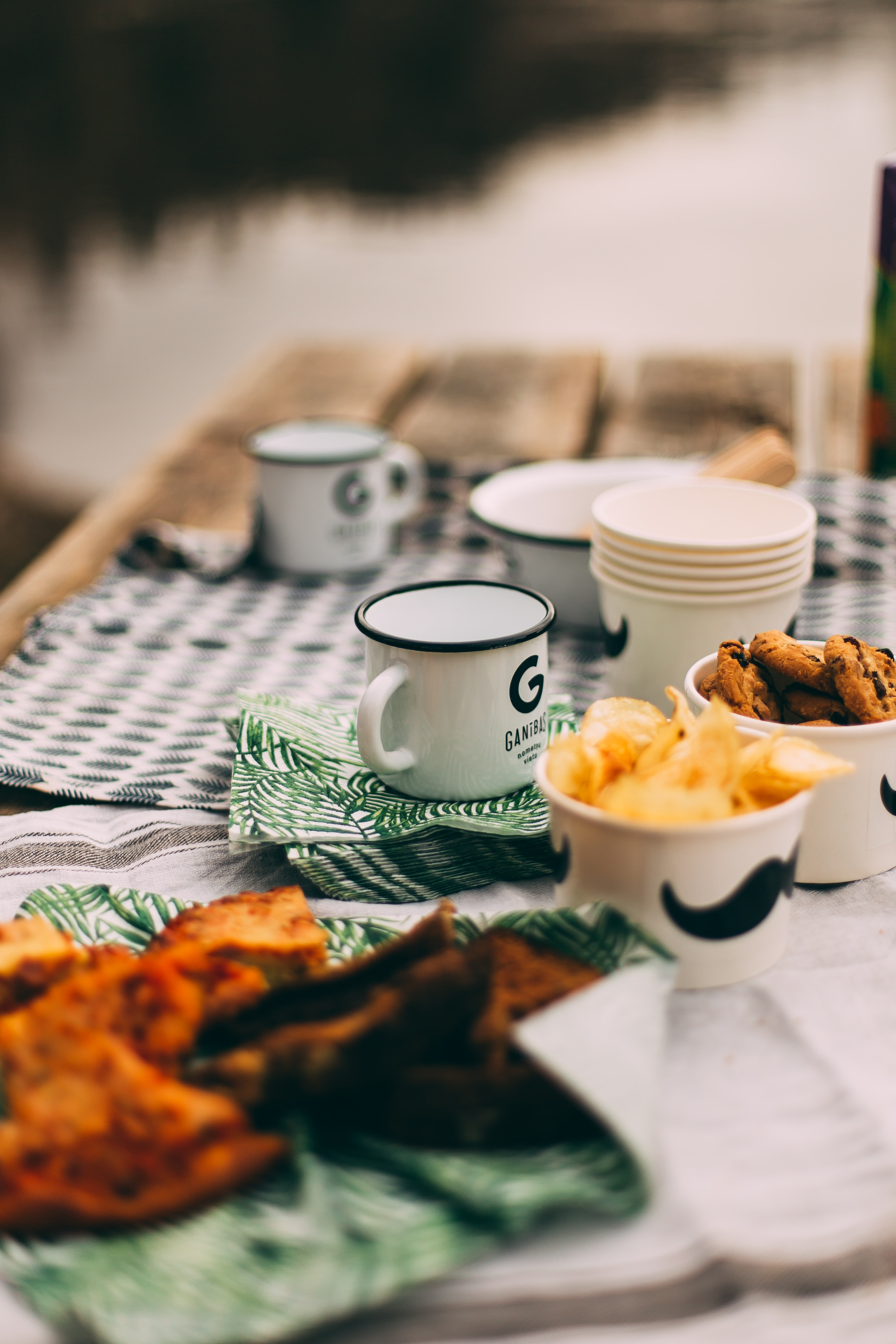 enamel-coated mugs and plastic cups on table selective focus photography