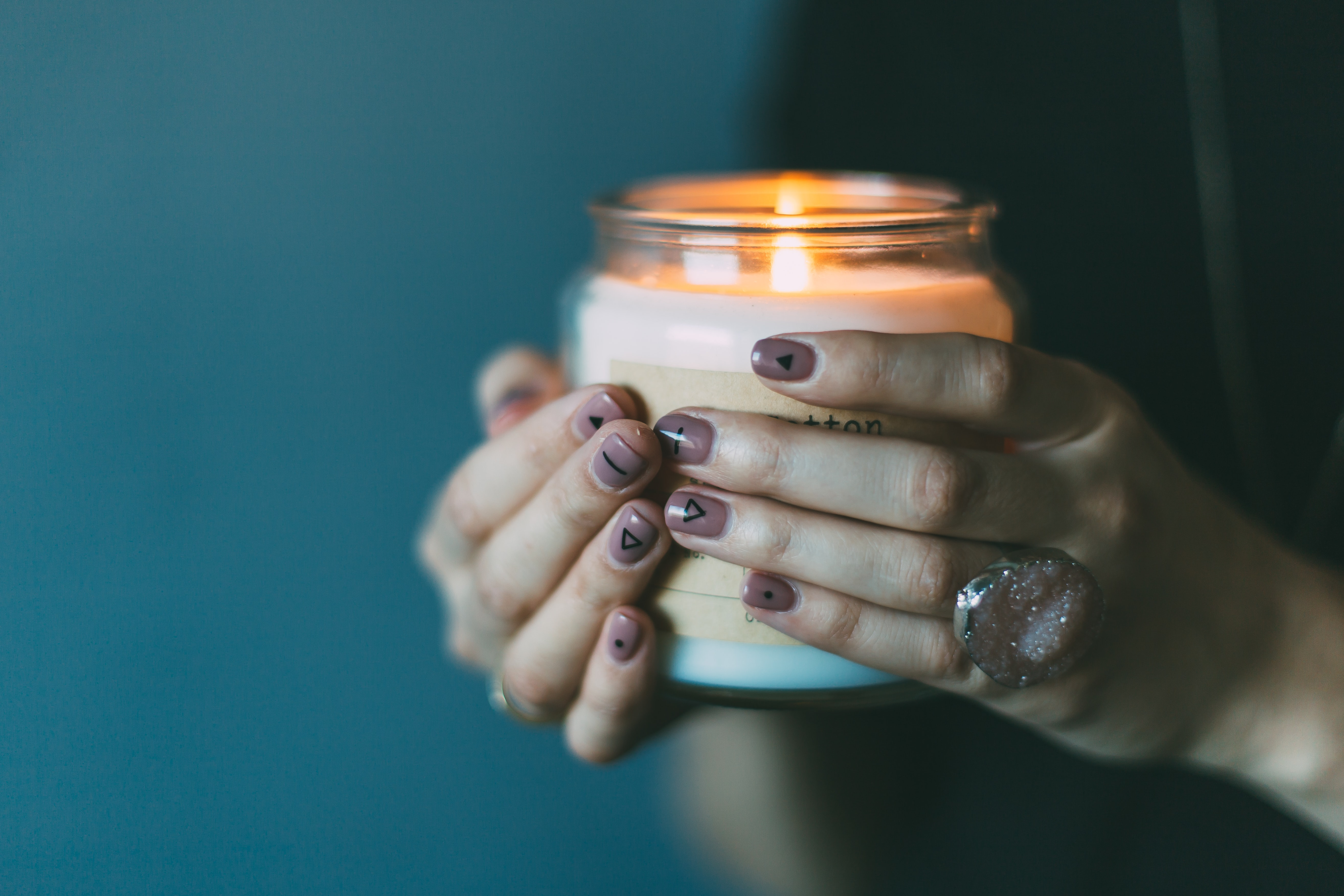 Woman wearing stone ring and painted nails holds lit candle in dark light