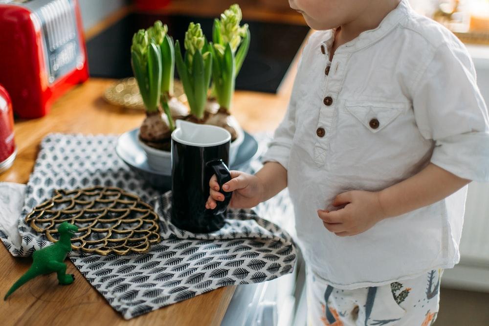 child holding black and white ceramic mug while standing near desk