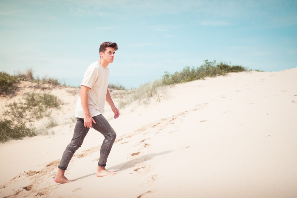 man wearing white t-shirt standing on sand field during daytime