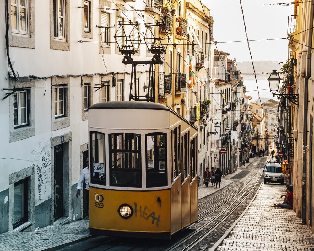 white and brown tram in between buildings at daytime