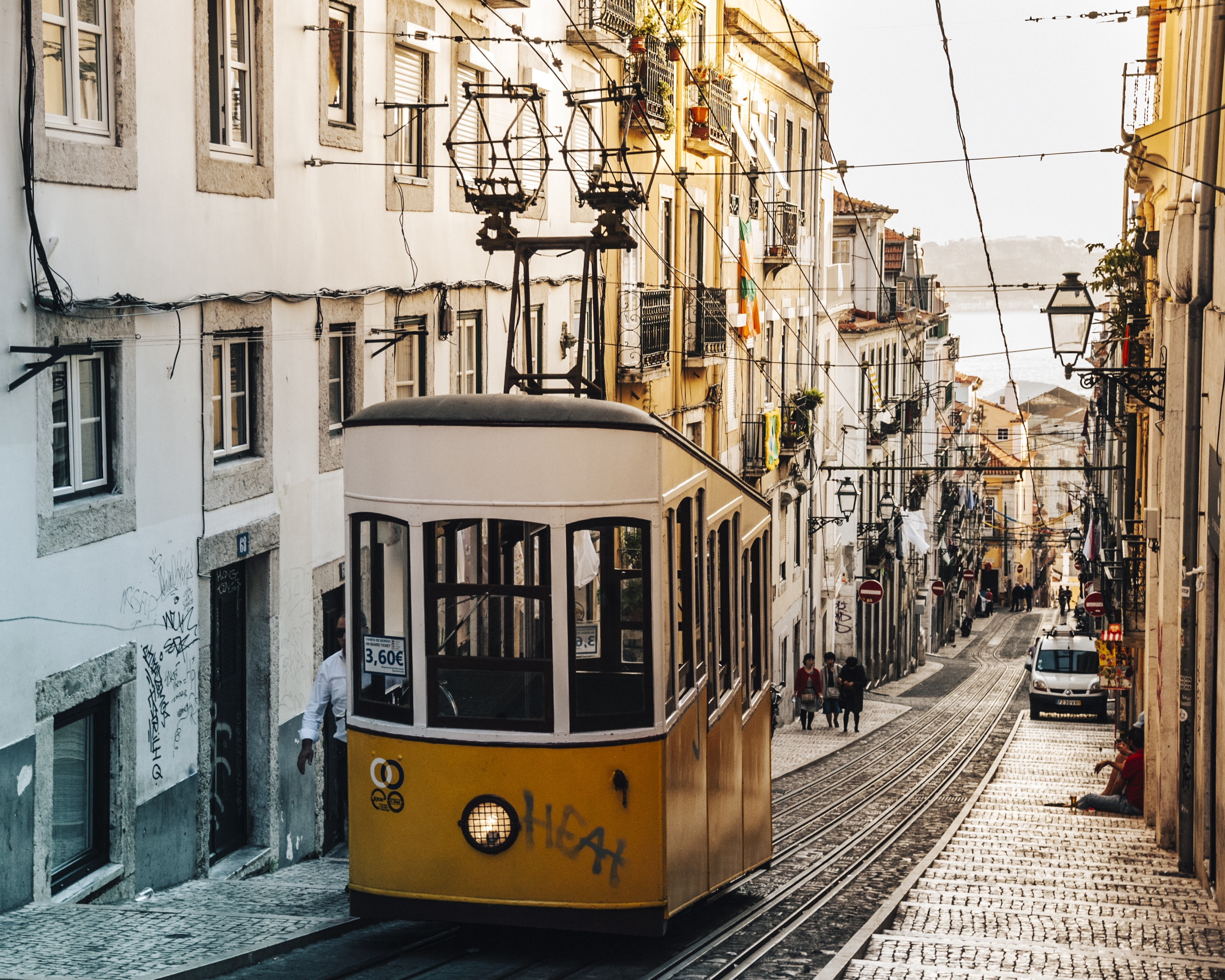 Yellow tram carriage suspended at the top of a narrow street with traditional architecture, Lisbon, Portugal