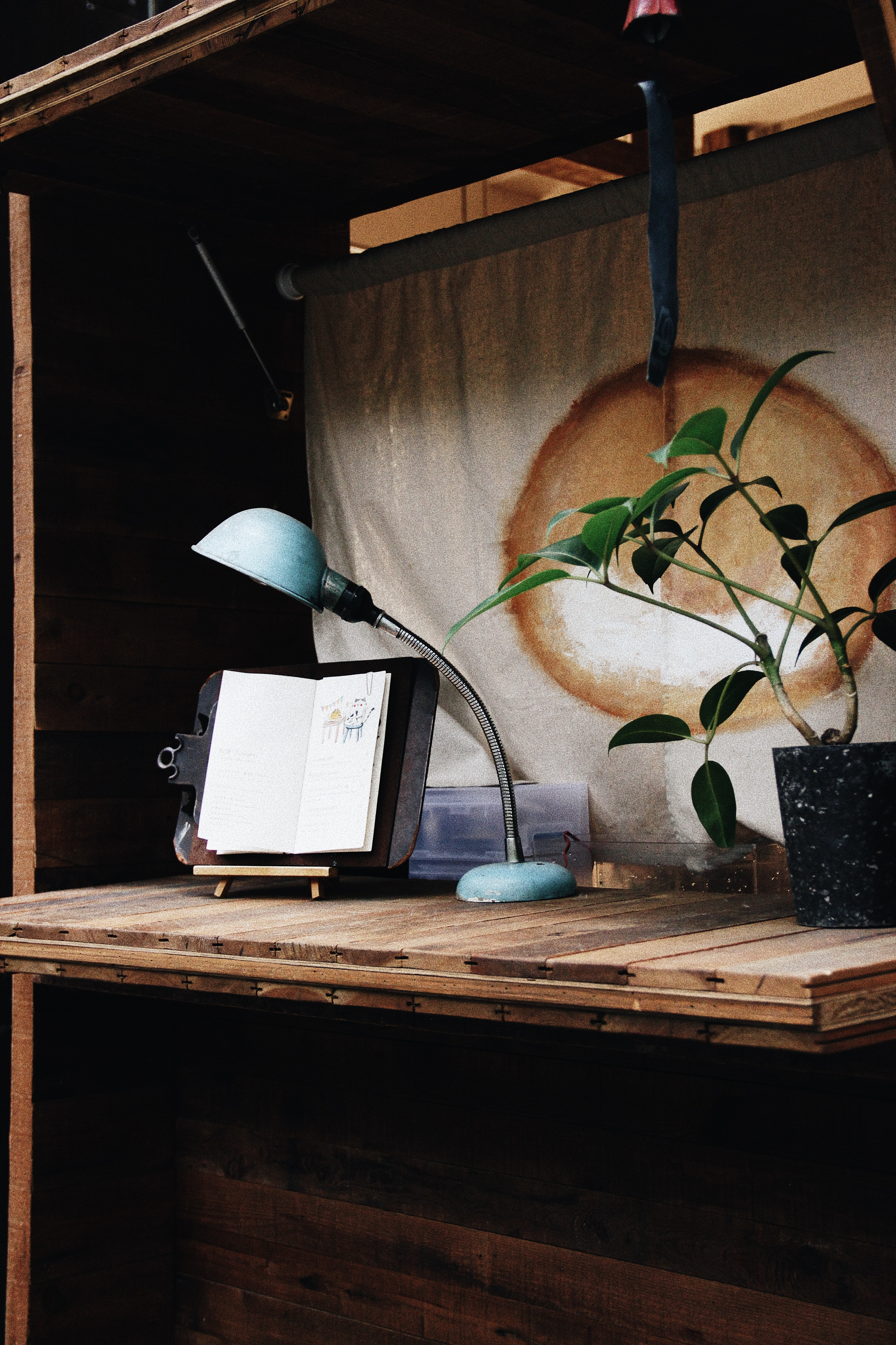 A vintage desk with an open notebook, a potted plant and a lamp