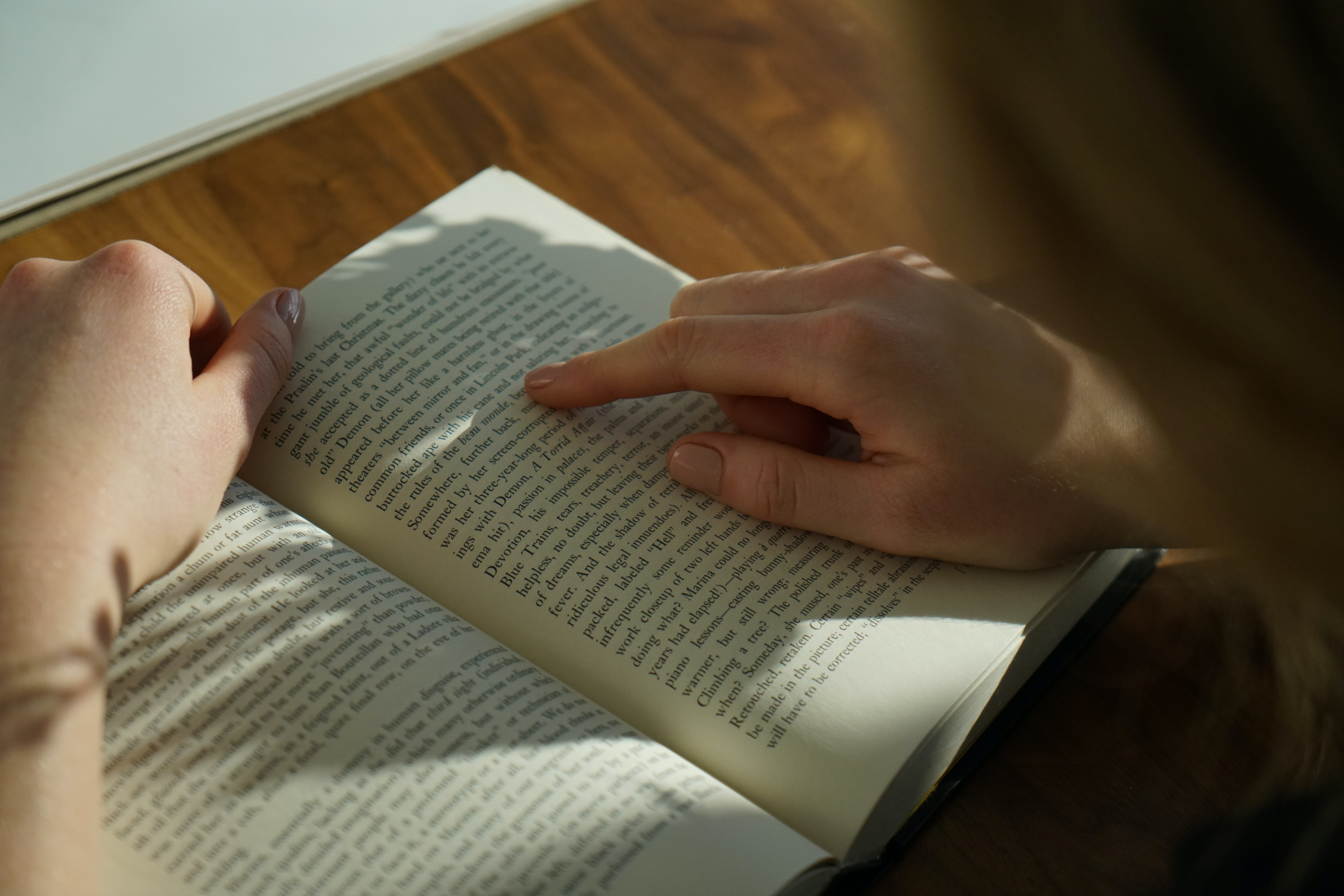 Person reading a book uses their finger to keep their page