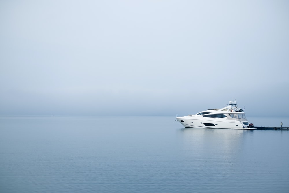 white yacht on body of water