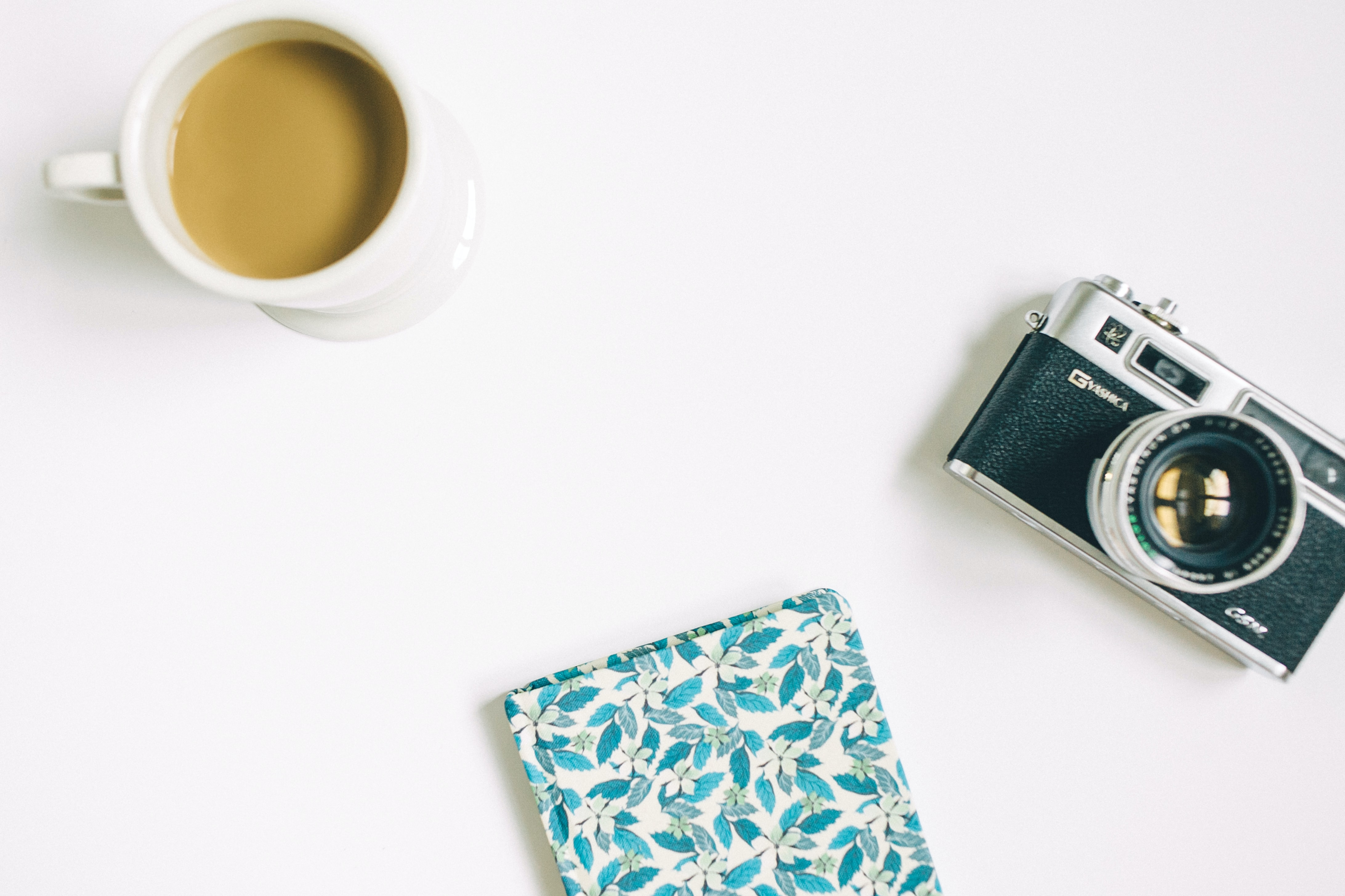 black and grey SLR camera, floral notebook, and white ceramic mug