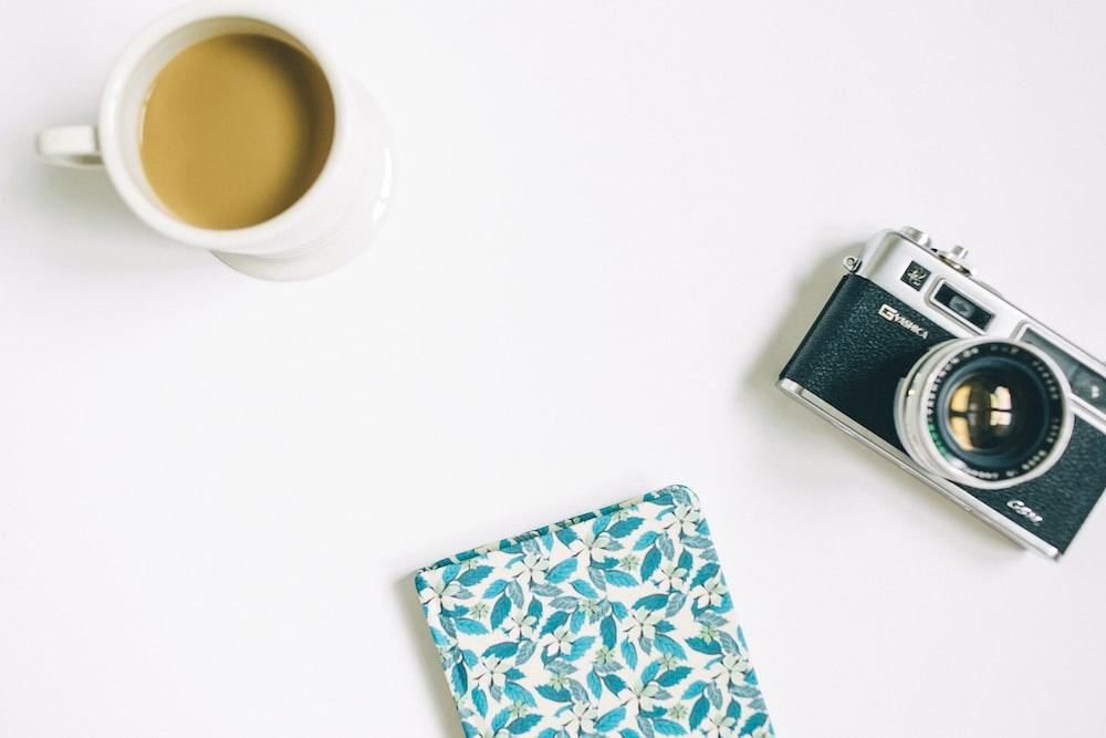 black and grey SLR camera, floral notebook, and white ceramic mug