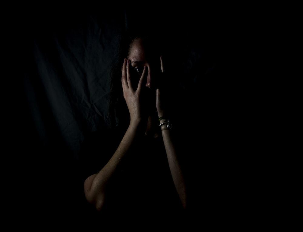 暗い部屋で彼女の顔を保持している女性