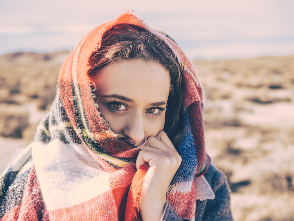 woman covering her face with red and white scarf