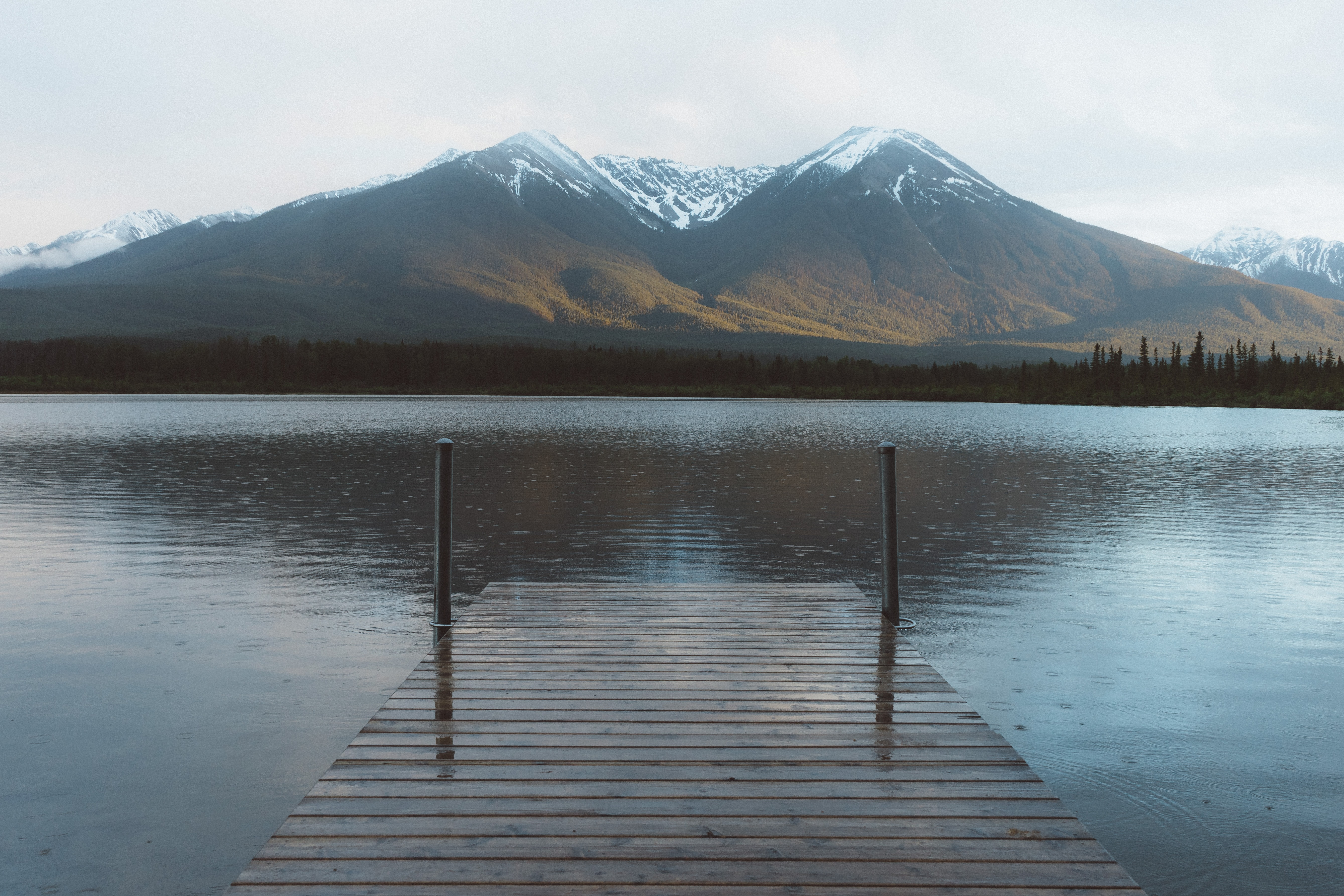 A dock over calm water that looks out to the snowcapped mountains that are reflected in the lake
