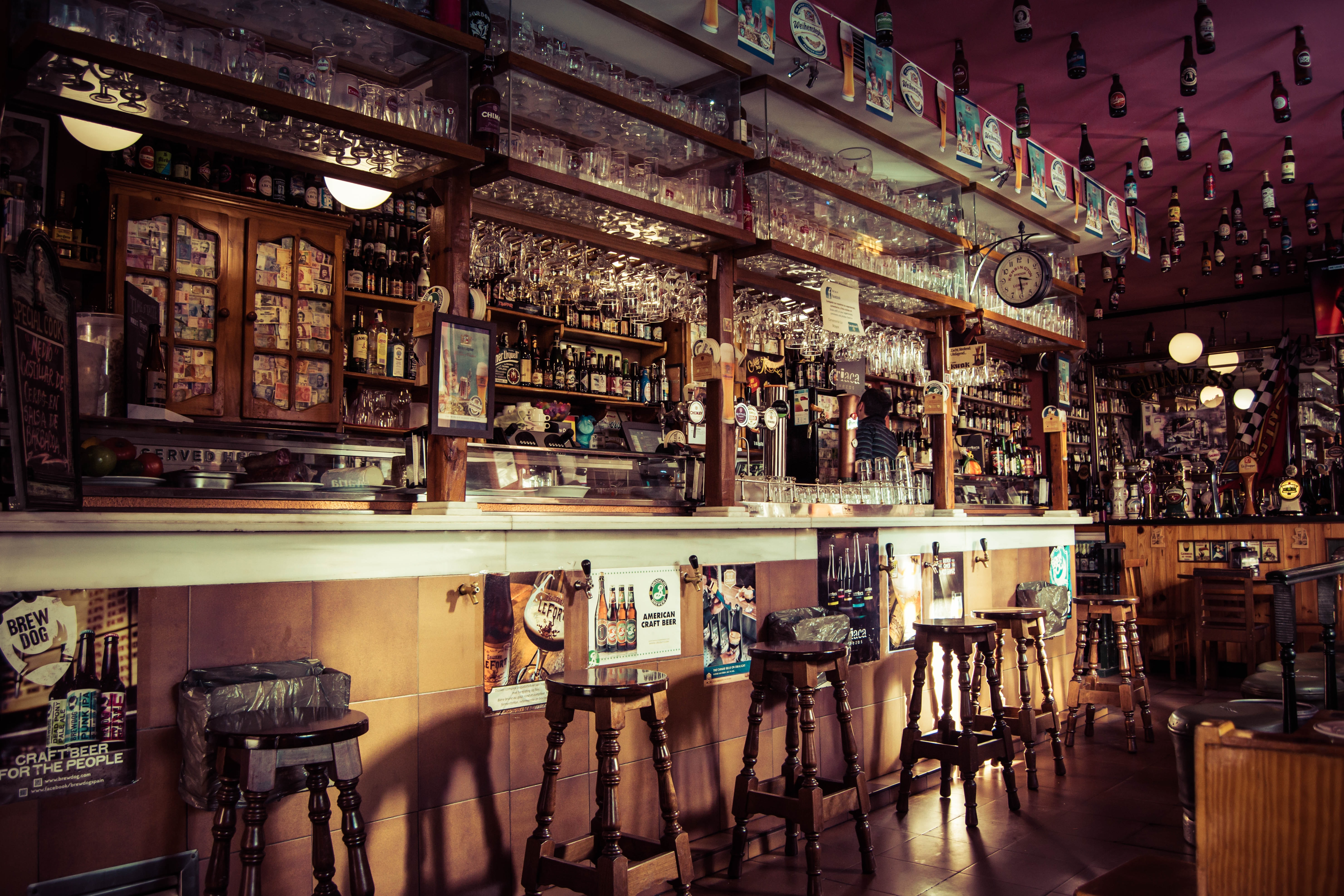 The interior of a bar with stools, glass cups and empty bottles attached to the roof in Madrid