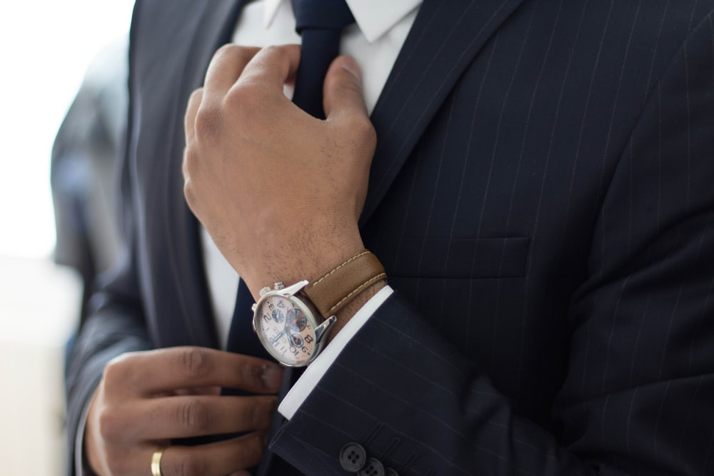 黒のスーツと時計を身に着けている男