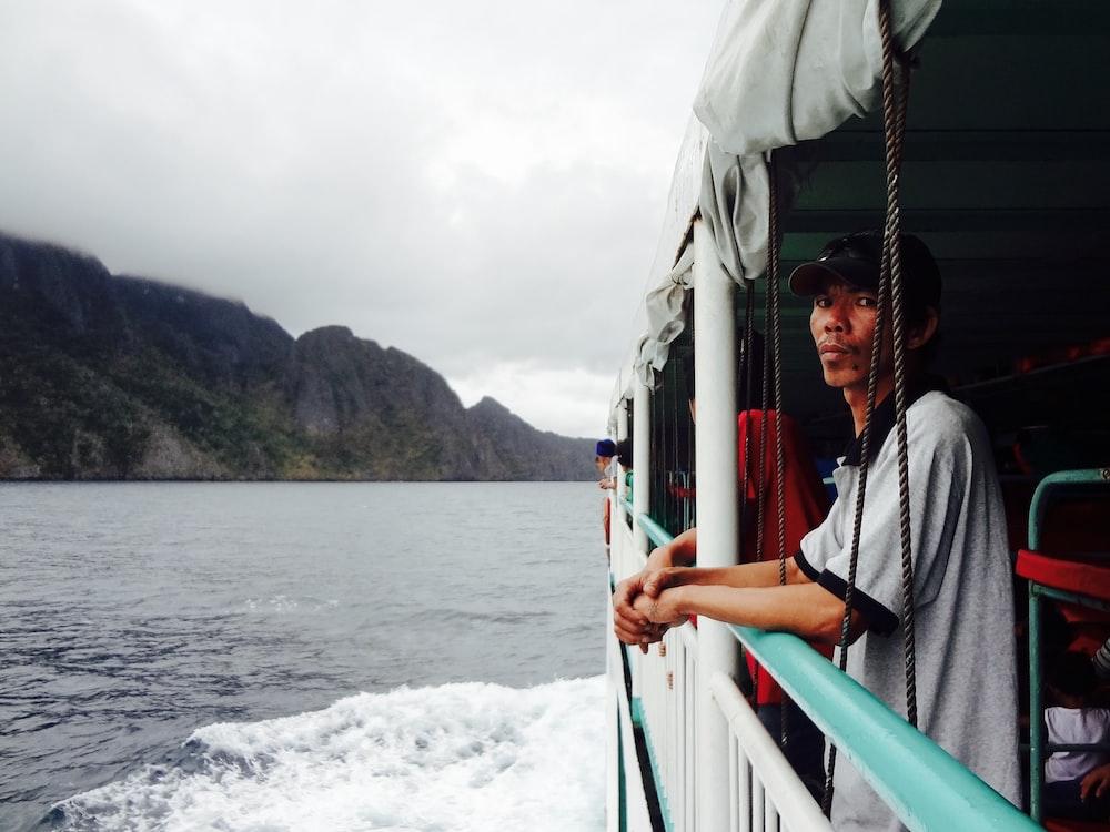 man wearing gray polo shirt standing beside boat on sea