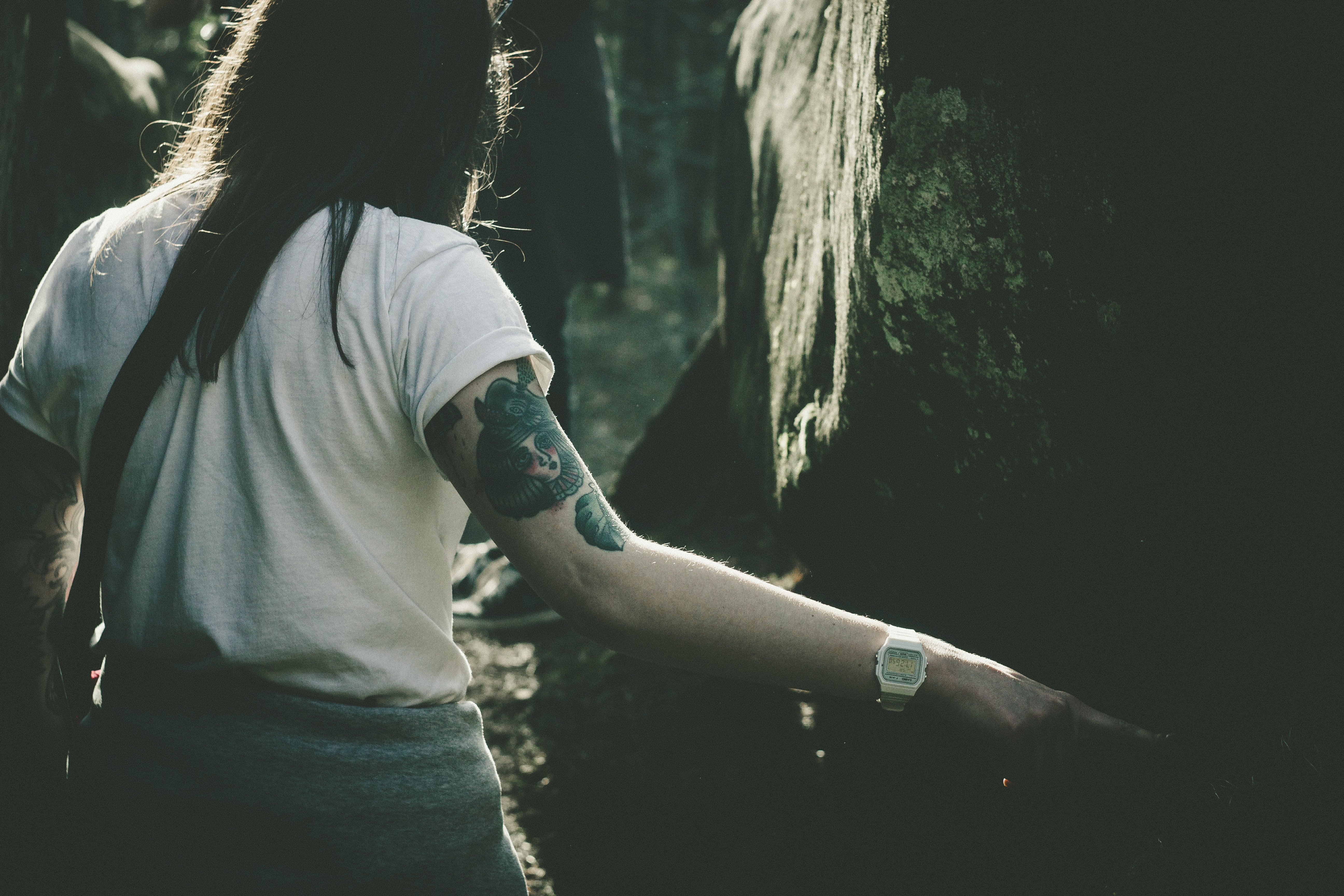 Woman with various tattoos on her arms walking through the forest of Dovbush Rocks