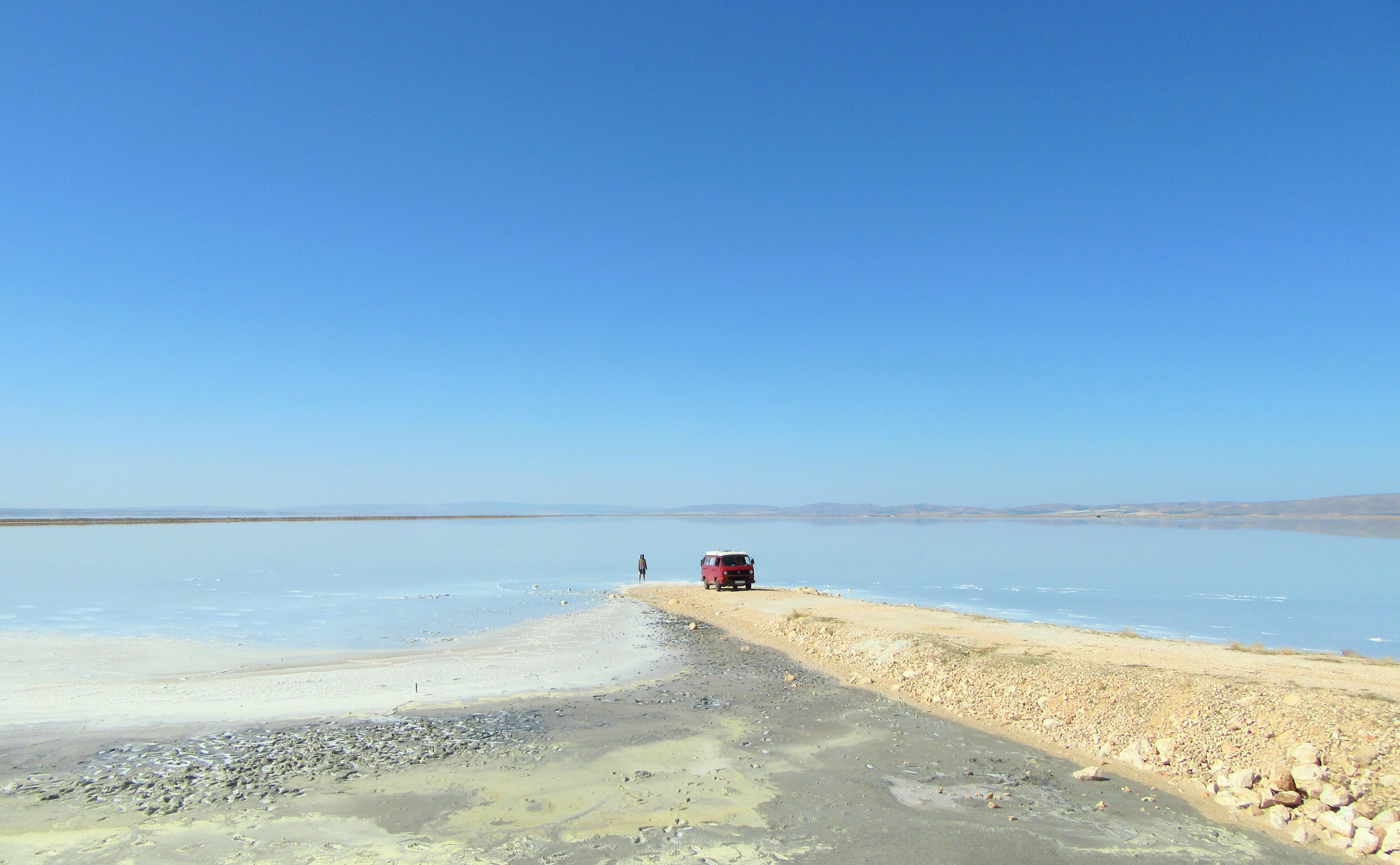 A distant shot of a person standing next to a red van parked on a sandy shore of a vast blue lake