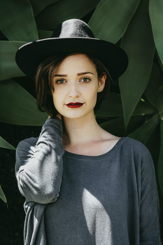 woman standing near trees wearing black hat