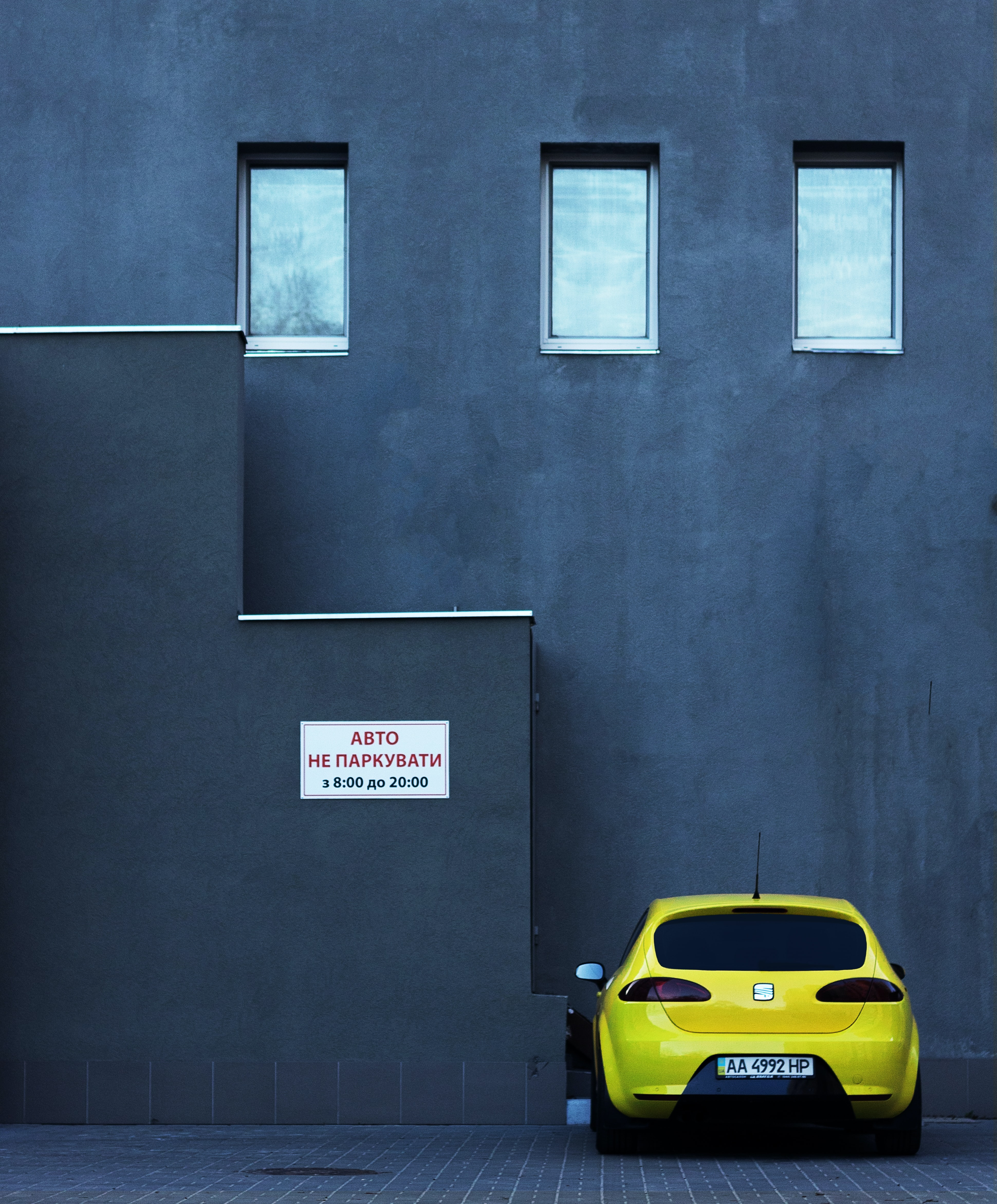 Parked yellow SEAT car next to gray urban building with three windows and white sign