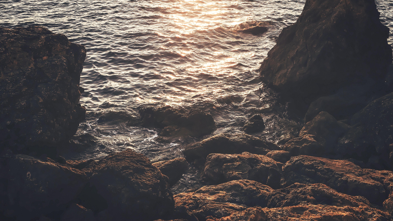rock near seat reflect light on water at daytime