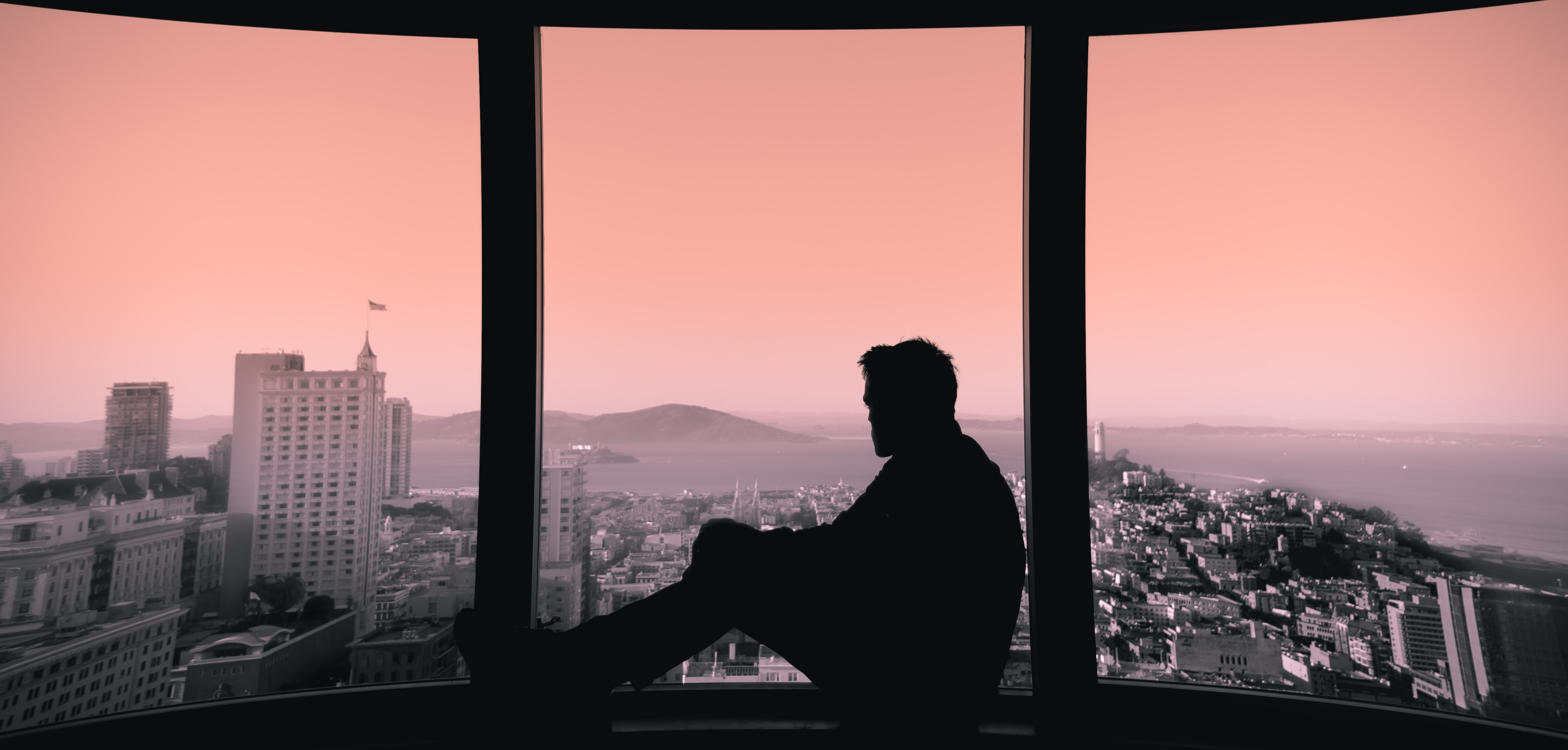 A silhouette of a man sitting on a windowsill and looking out the window