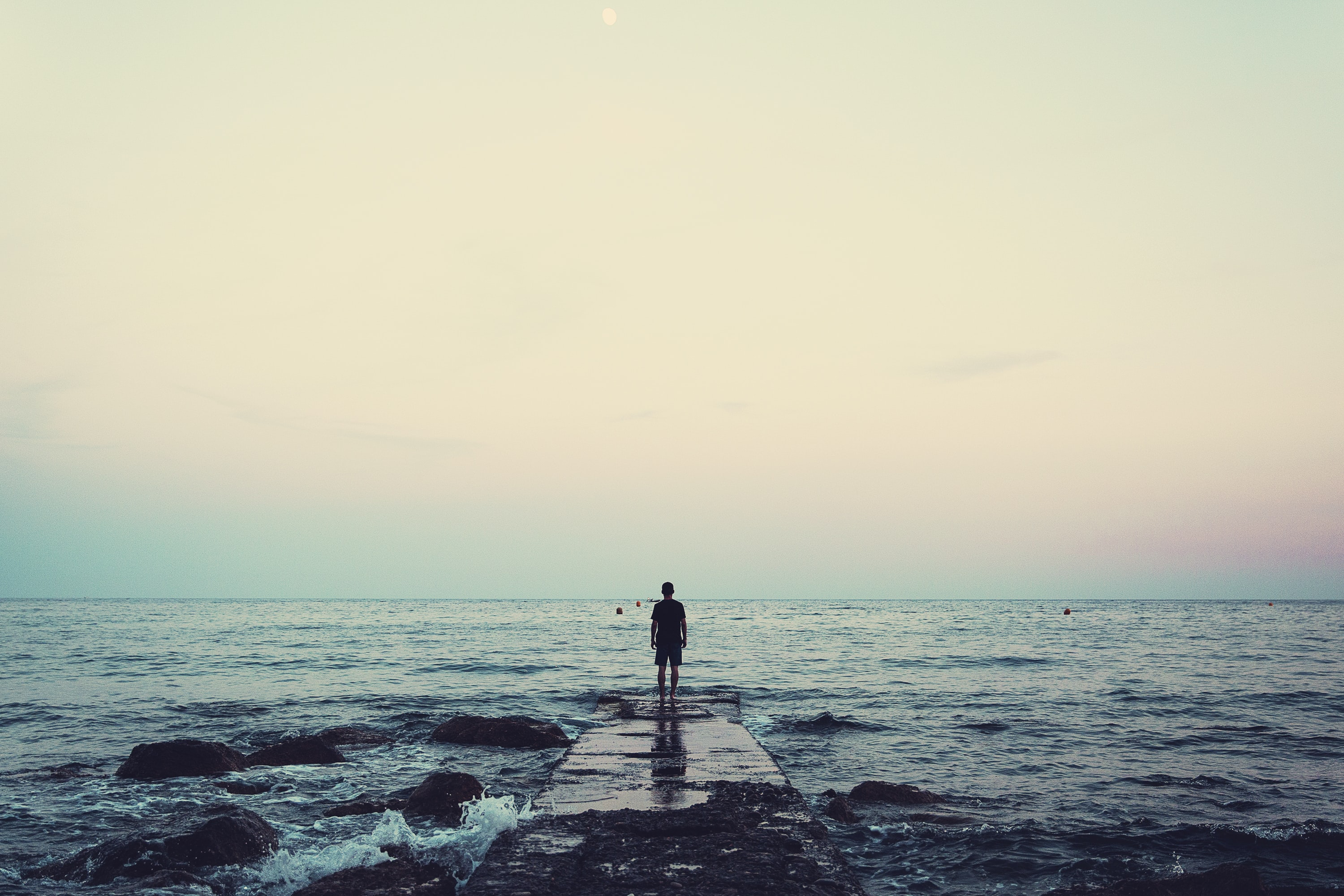 silhouette of person standing on sea dock under cloudy sky
