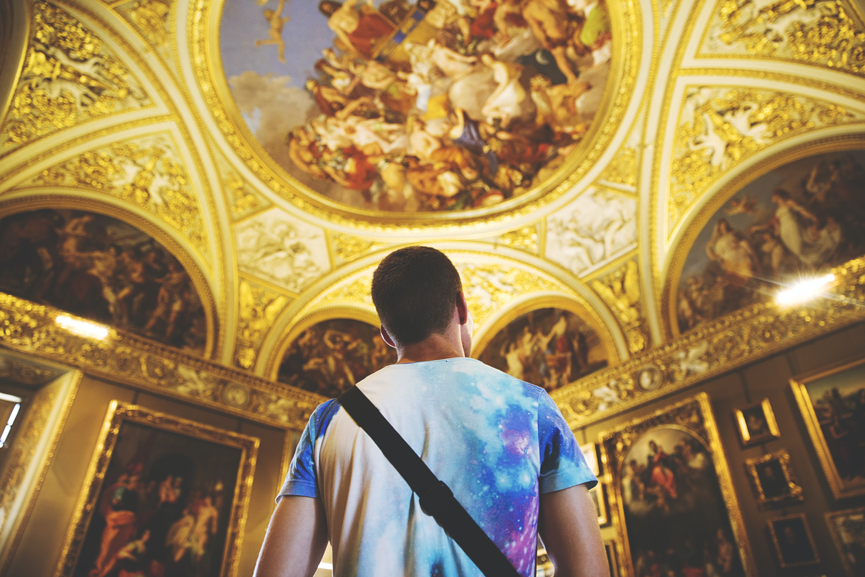 Man in multicolored tie dye t shirt looking at ornate, religious gold ceiling architecture in Florence