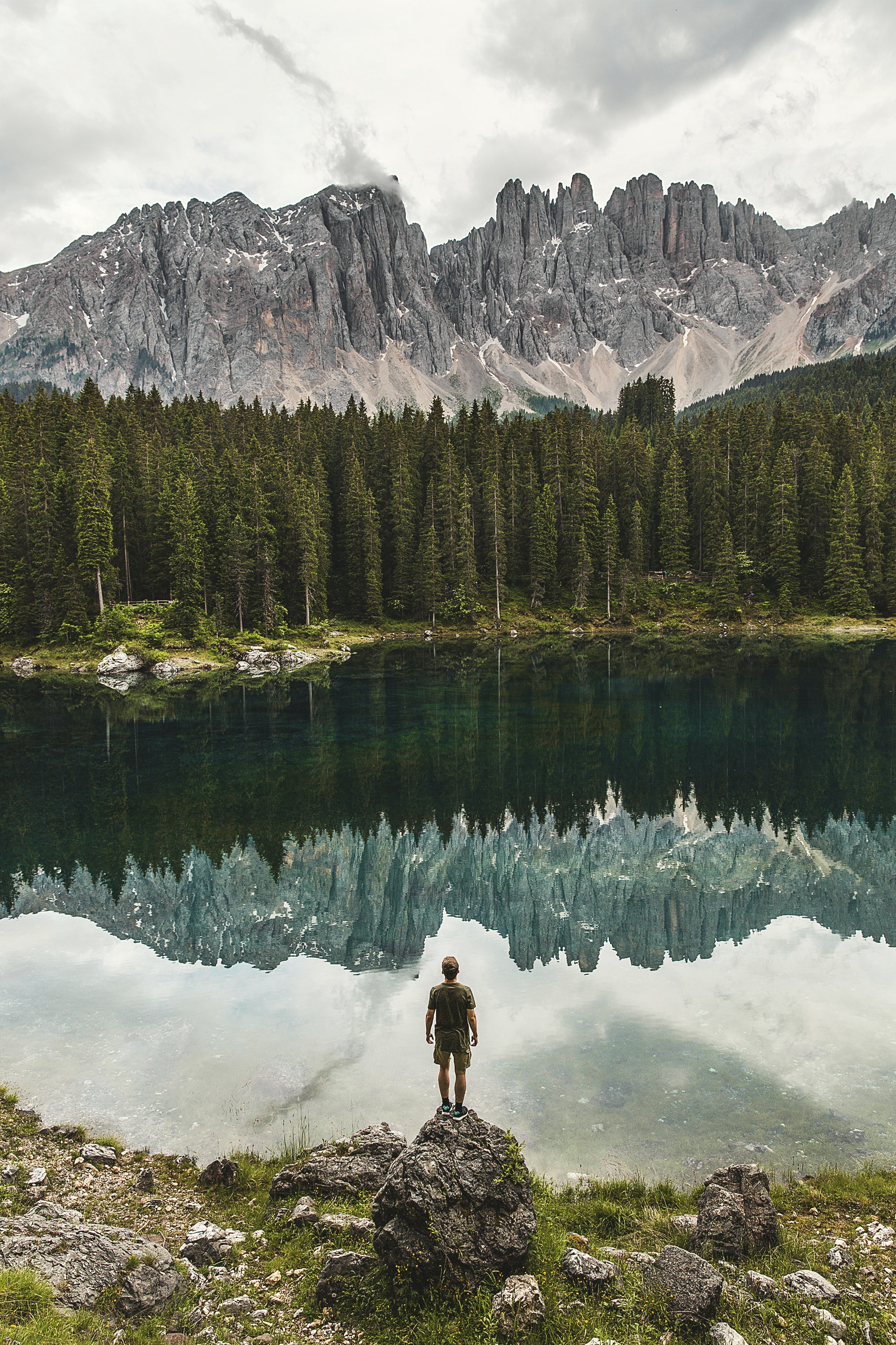 A man standing on a boulder staring at a mountain pond.
