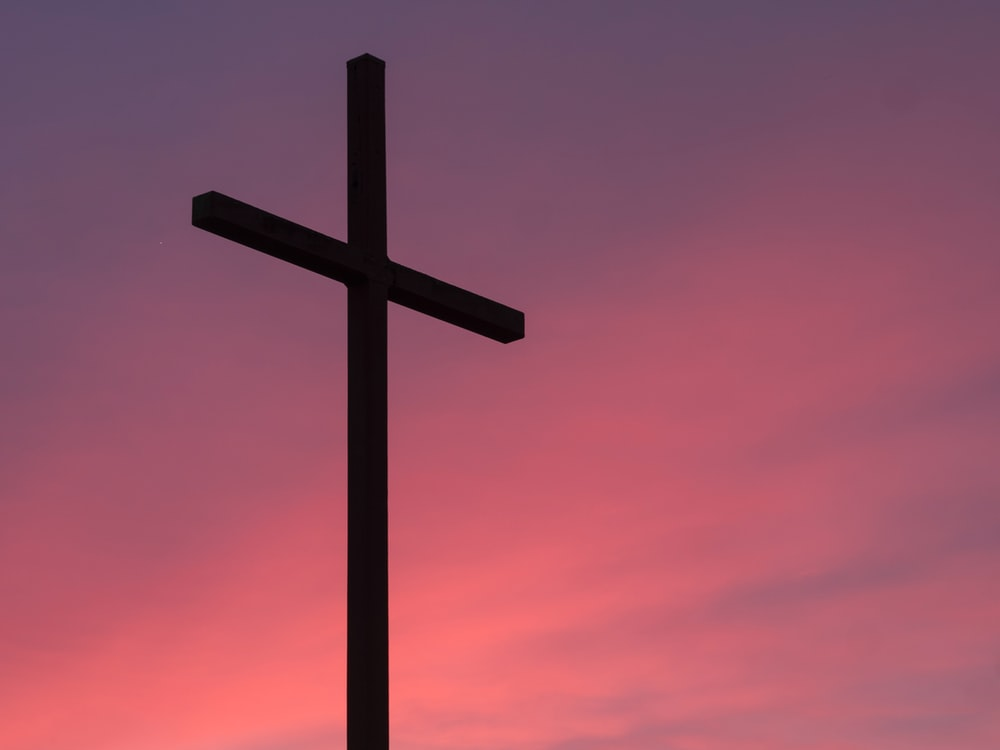 A cross against a pink and purple sky