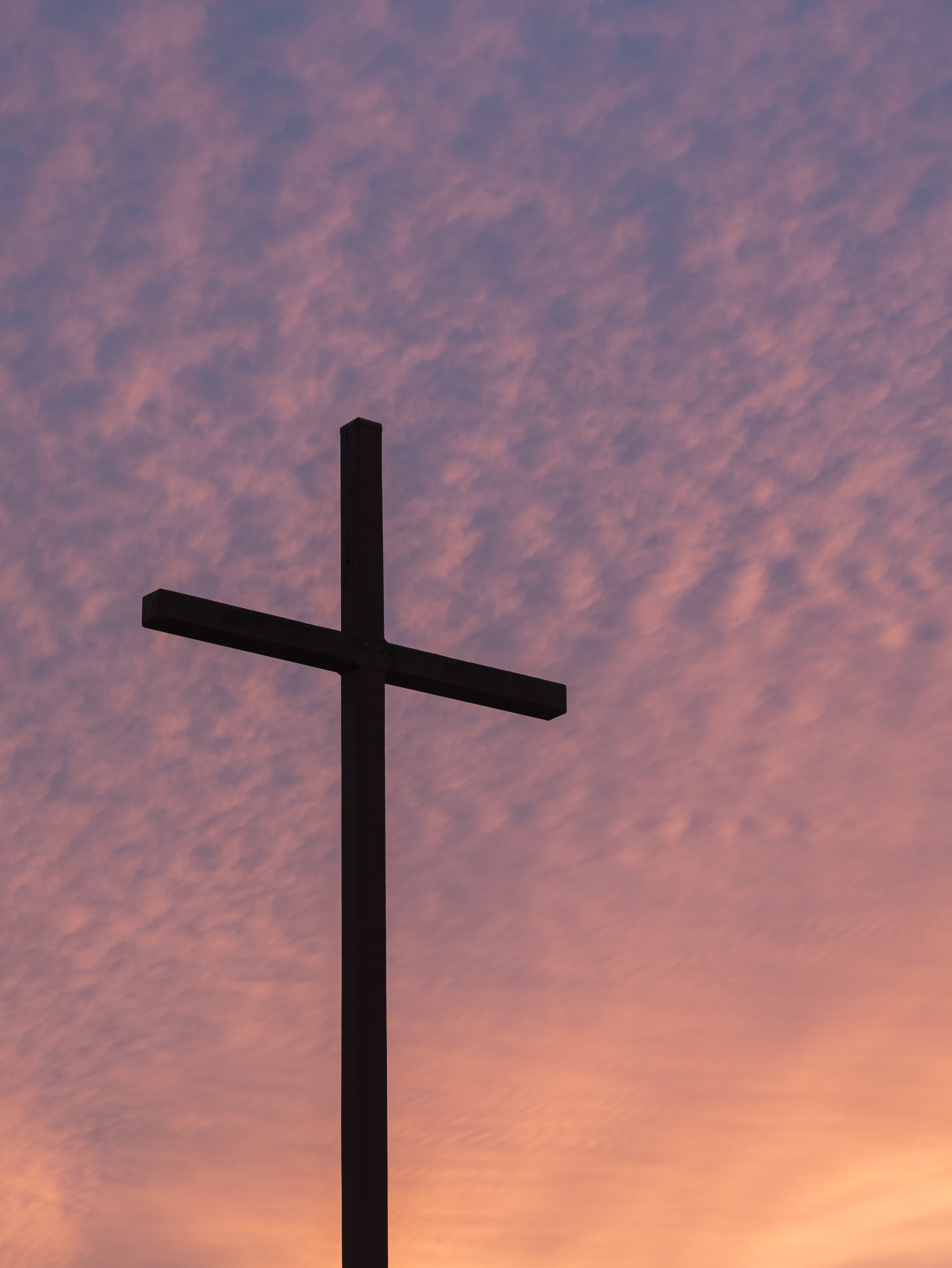 A crucifix of cross in front of a purple and orange sunset sky