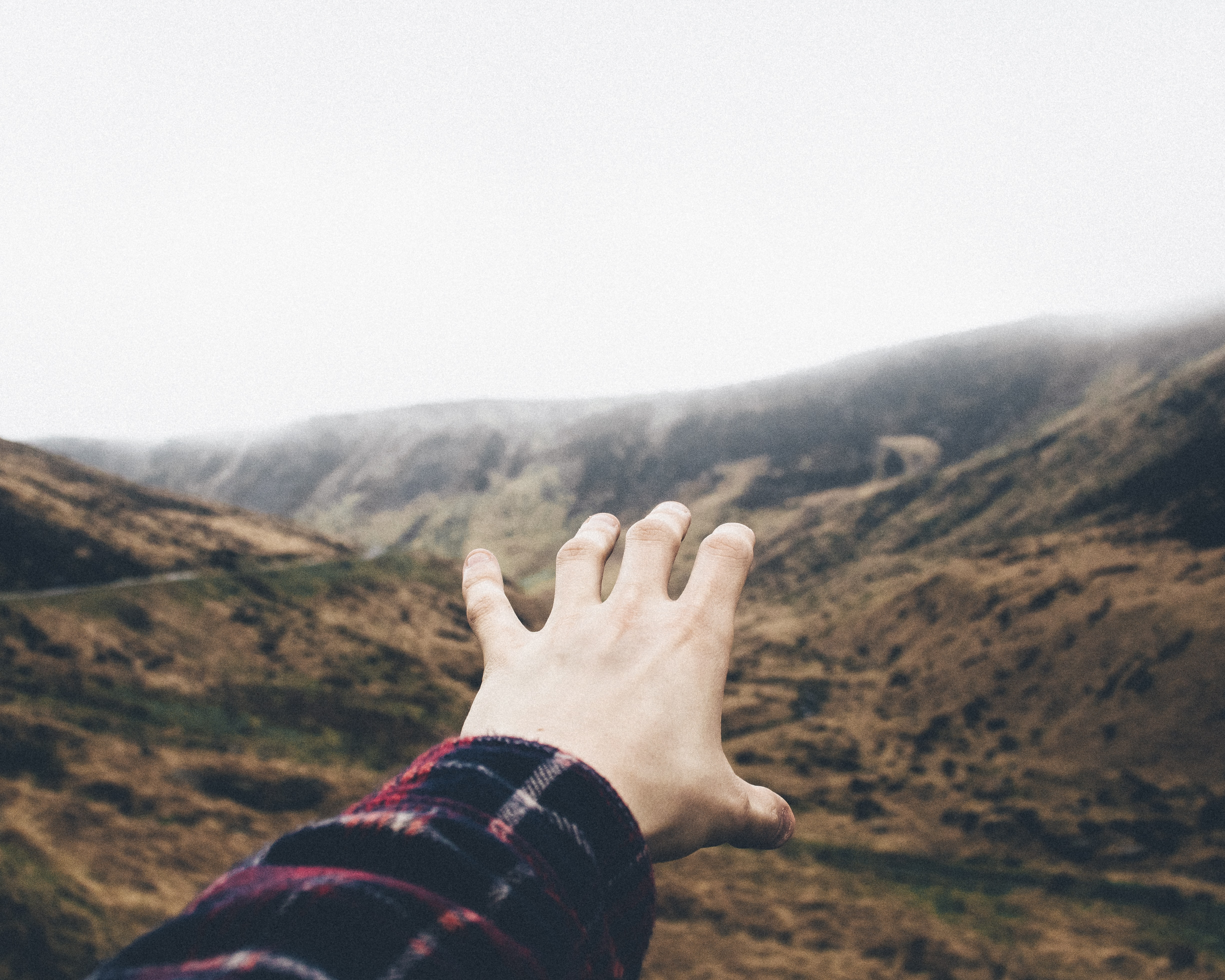 point of view photography of person raising hand towards mountains
