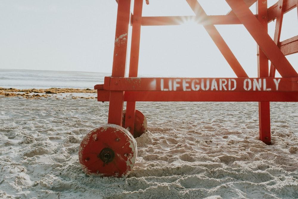 red lifeguard post near shoreline during daytime