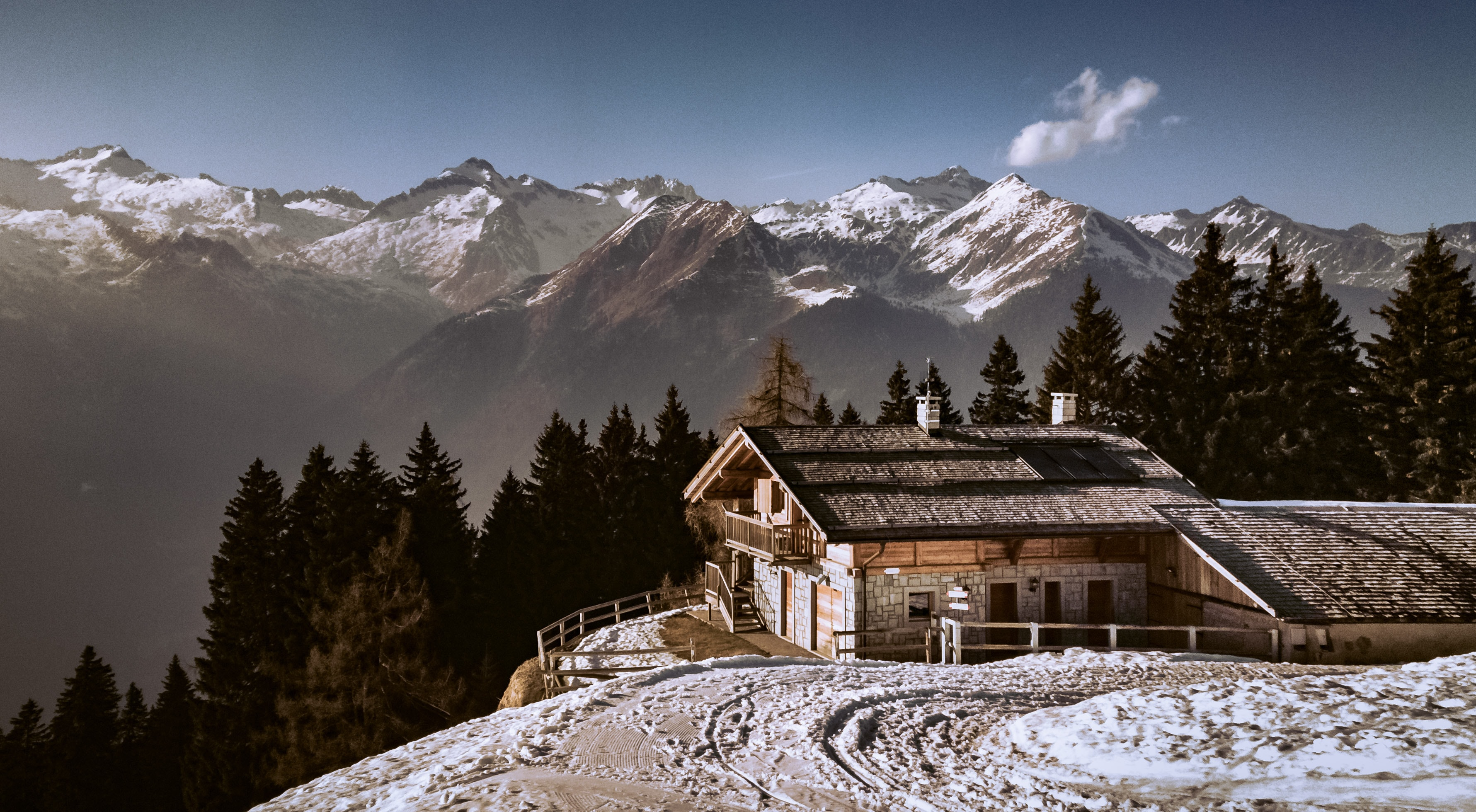 A building on a hillside in snowy mountains in Madonna di Campiglio