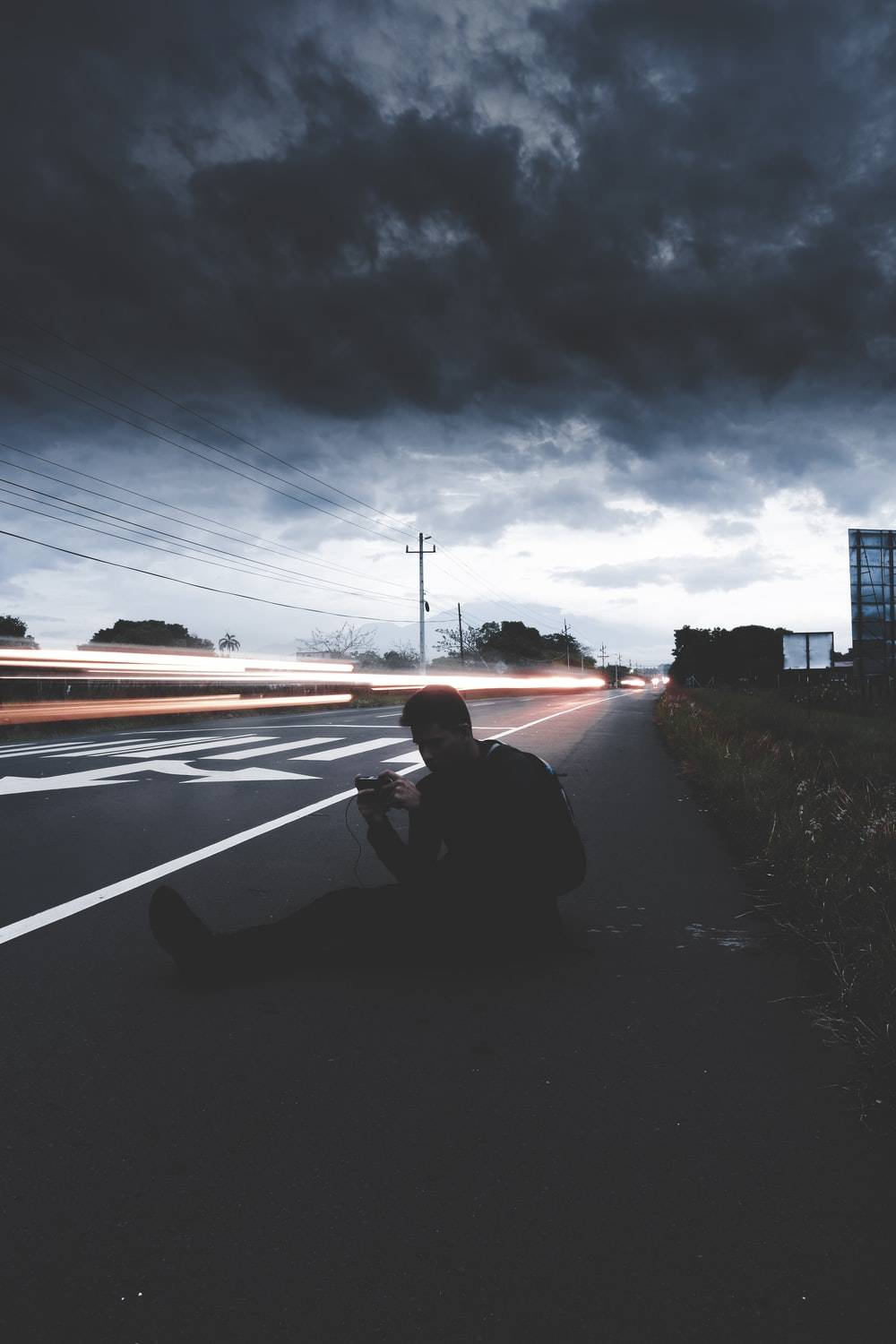 man sitting on road in time lapse photography