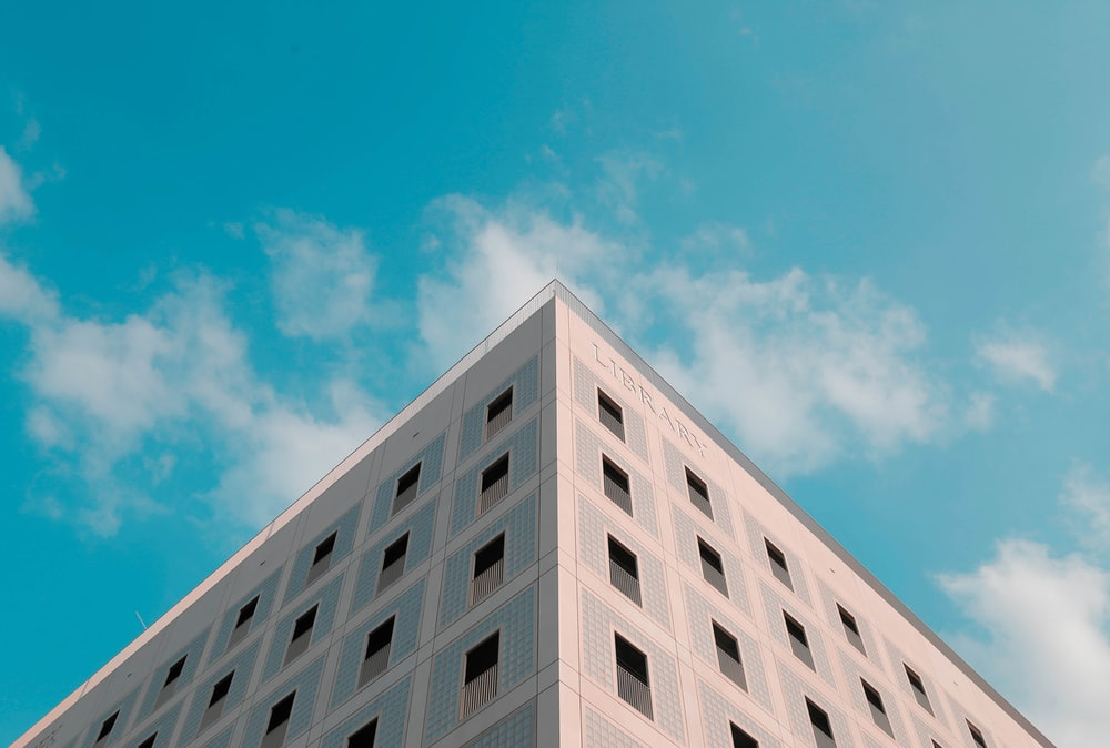 shallow focus photography of Library building under blue and white cloudy skies at daytime
