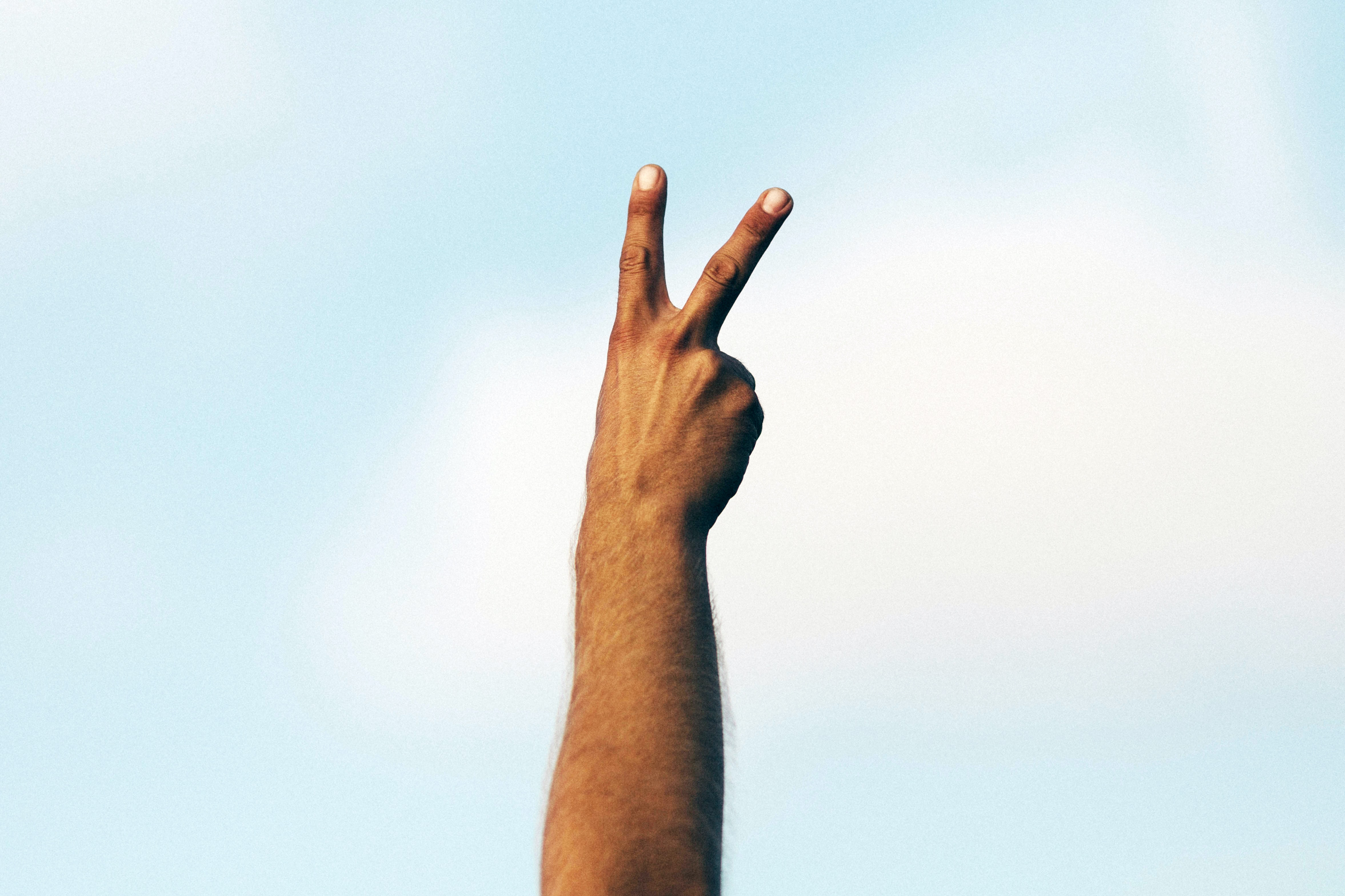 A hand with two fingers raised in a peace sign