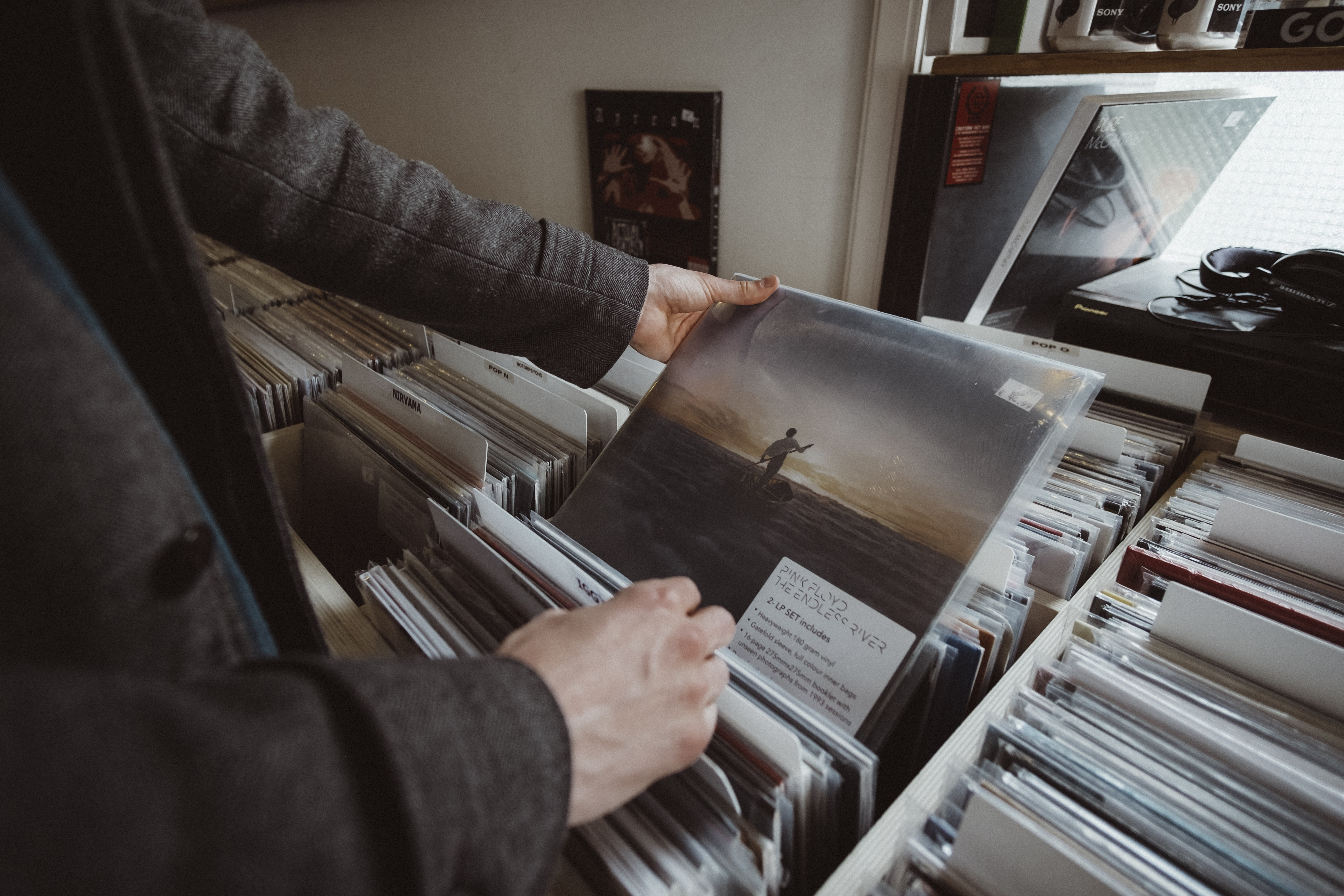 A man holding a Pink Floyd vinyl while browsing in a record store