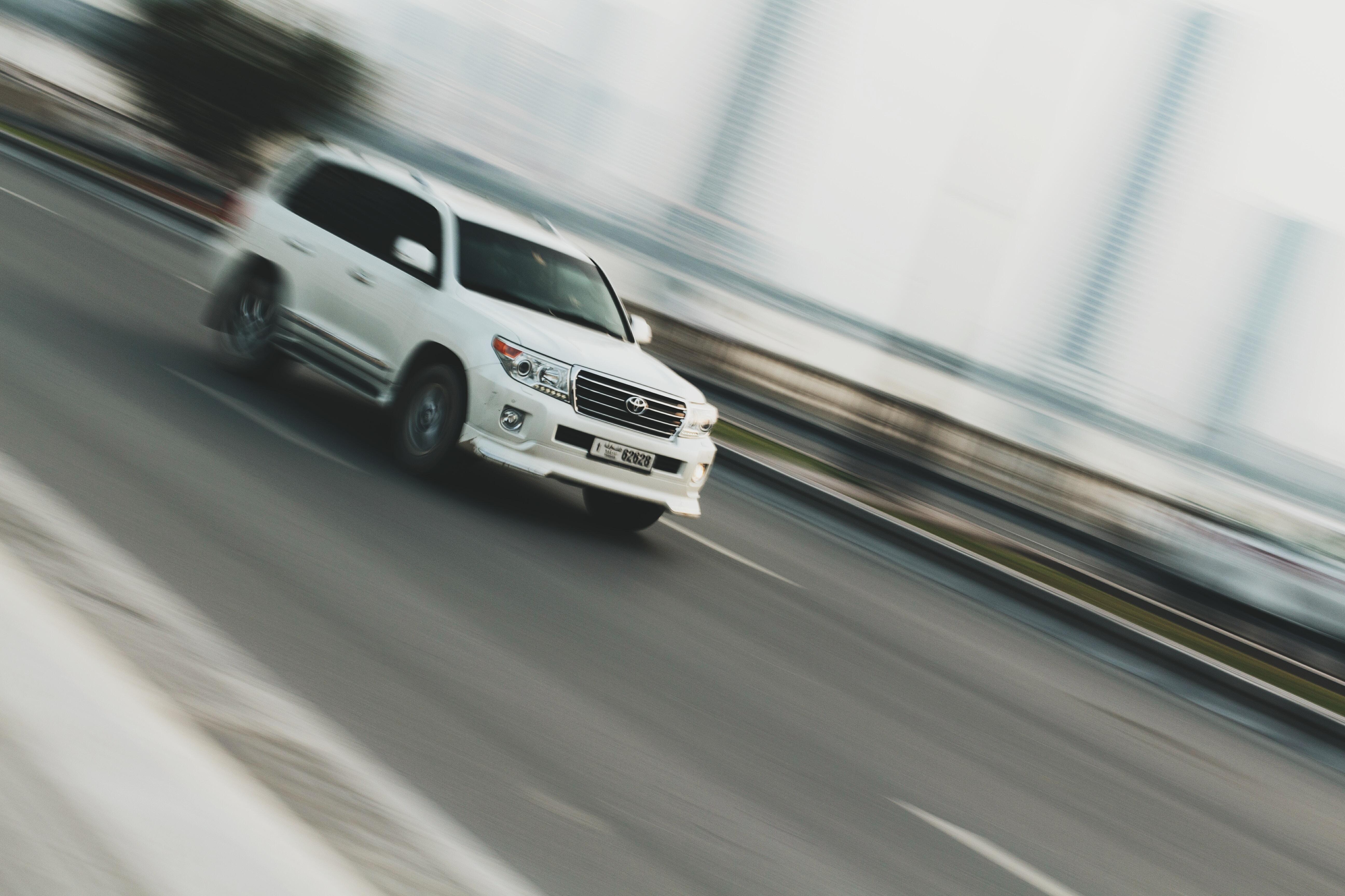 A blurry shot of a white SUV driving on a road in Al Qasba