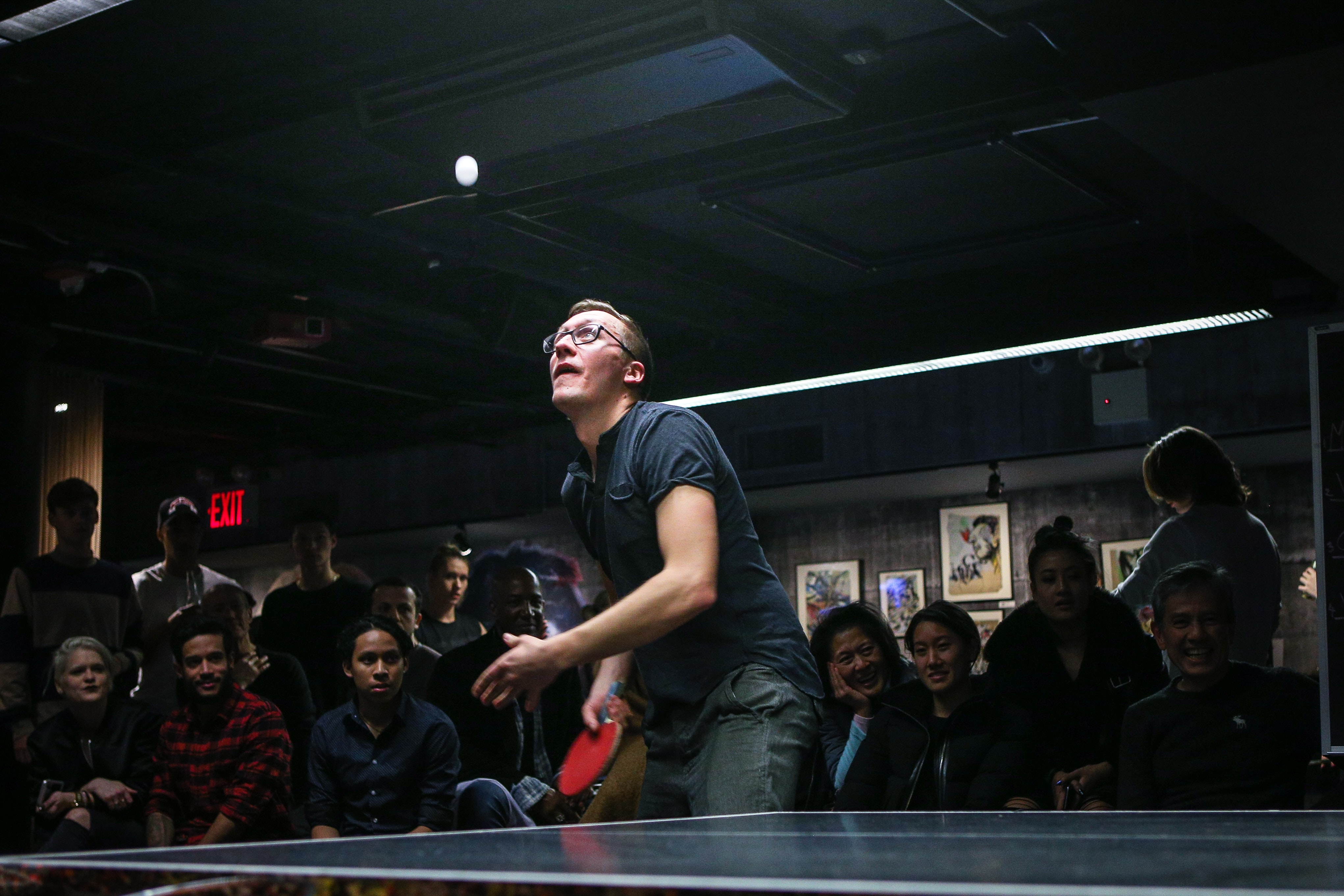 man about to paddle ping pong ball surrounded by group of people