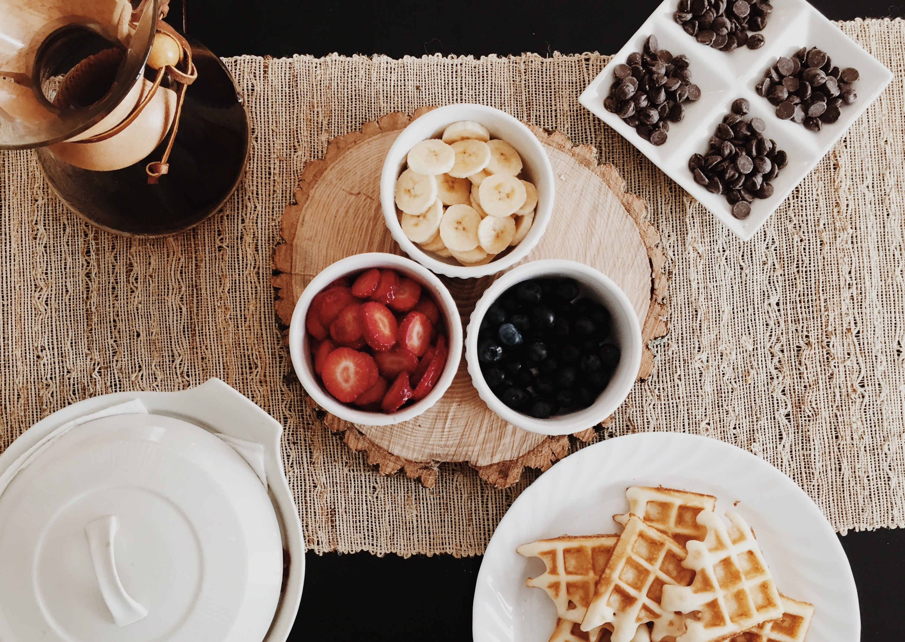 Flat lay of DIY waffle station with fruit, syrup, and chocolate chips