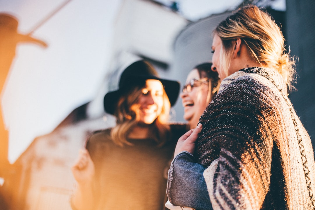 All about staying connected with your friends in your 30s - what is friendship like in your 30s and top tips for how to stay connected. 3 women laughing together.