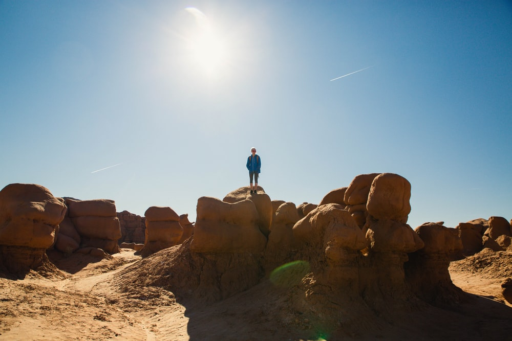 man standing on rock formation during daytime